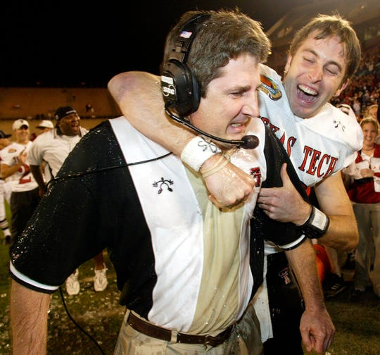 Texas Tech quarterback Kliff Kingsbury celebrates with head coach Mike Leach in the final minutes of the fourth quarter against Clemson at the Mazda Tangerine Bowl on Monday, Dec. 23, 2002, in Orlando, Florida.