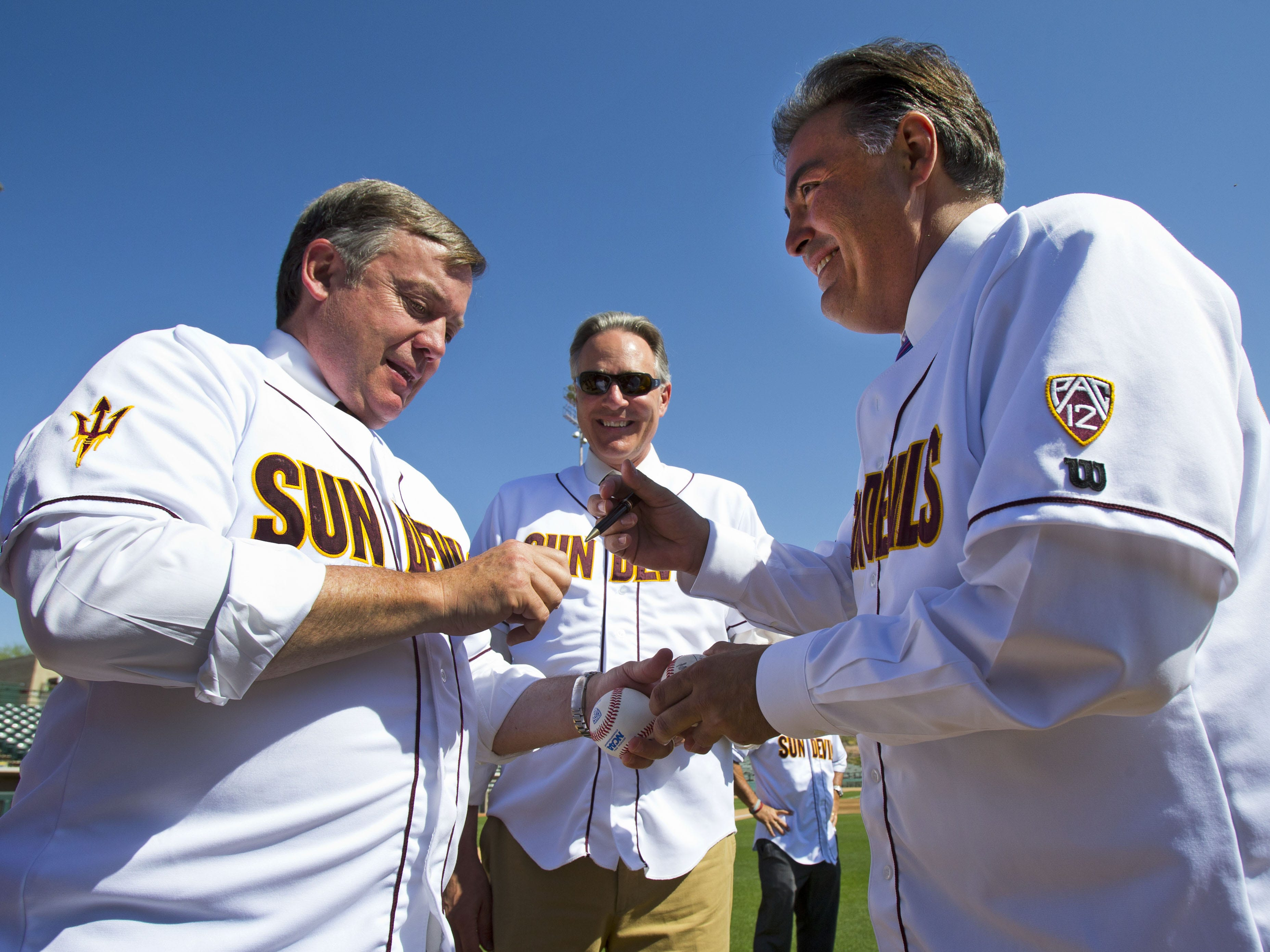 ASU President Michael Crow (left) signs a baseball for former Phoenix City Manager David Cavazos (right) in 2013. This was after a press conference that announced ASU's baseball team's move to the Phoenix Municipal Stadium.