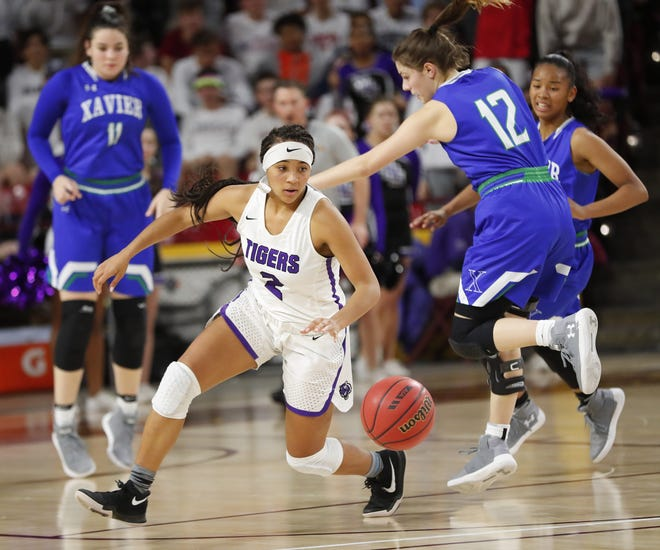 Millennium's Jasmine Singleton (2) dribbles away from Xavier's Addy Putnam (12) during the 6A girls basketball semifinal at Wells Fargo Arena in Tempe, Ariz. February 21, 2018.