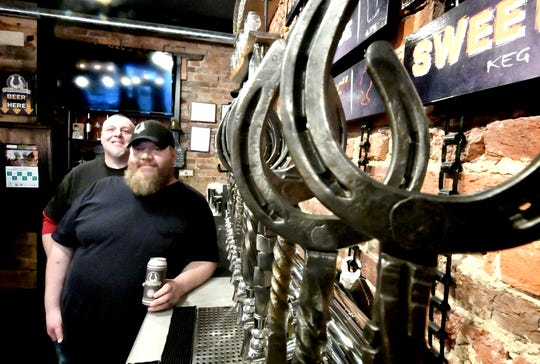 Gift Horse Brewing Company co-owner Jason Snyder and brewer Josh Jacobs, left, pose with the signature beer taps at the York City brewery Tuesday, Jan. 8, 2019. Snyder says that due to the government shutdown, the Alcohol and Tobacco Tax and Trade Bureau has ceased operations, delaying approval of labels for four beers he is planning to market. Bill Kalina photo