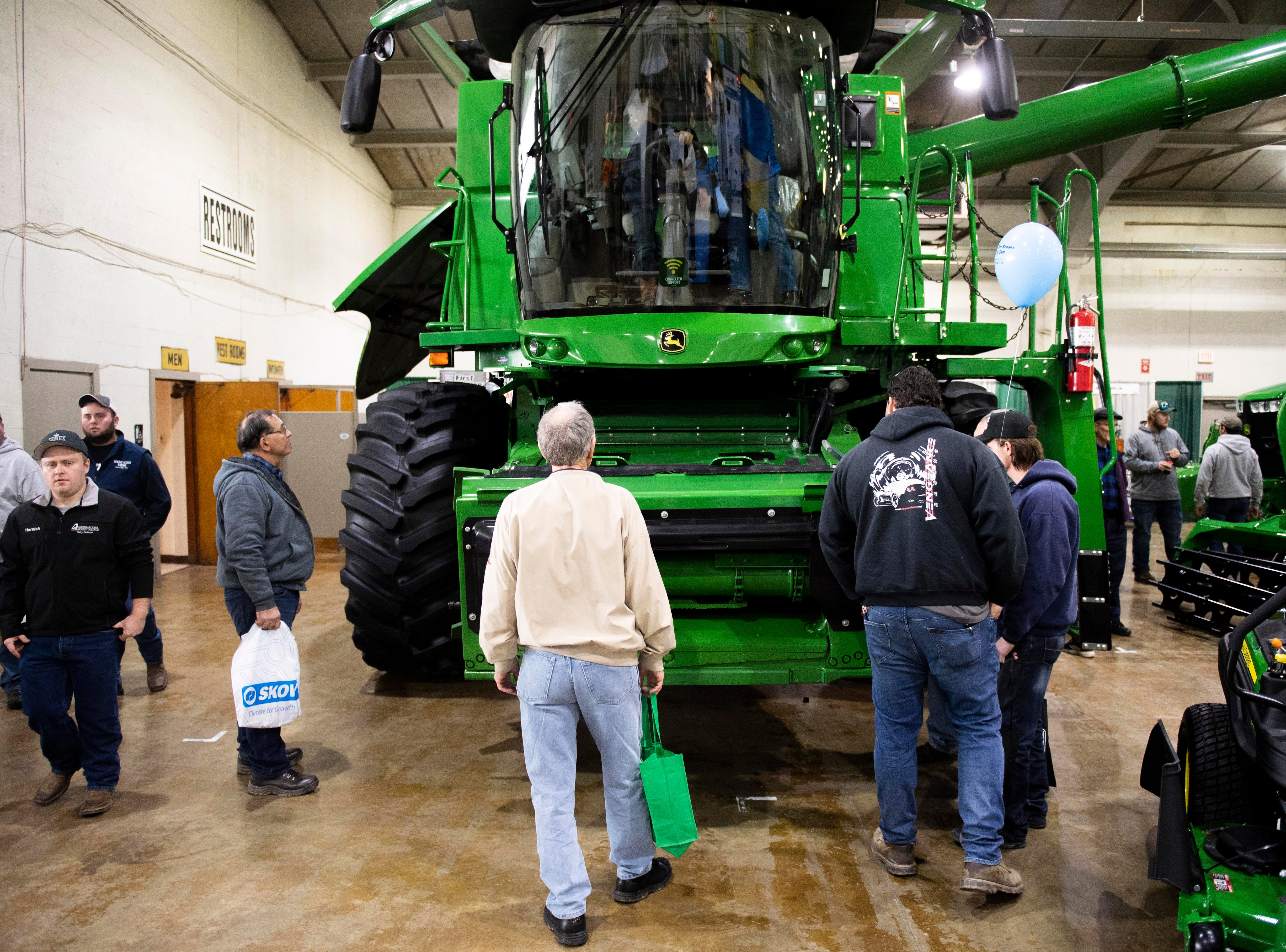 Keystone Farm Show attendees glaze around at the John Deere section of the farm show, Tuesday, Jan. 8, 2019. The Keystone Farm Show has nearly 420 vendors and is expected to bring up to 15,000 people to the York Expo Center. The show runs through Thursday, Jan. 10.
