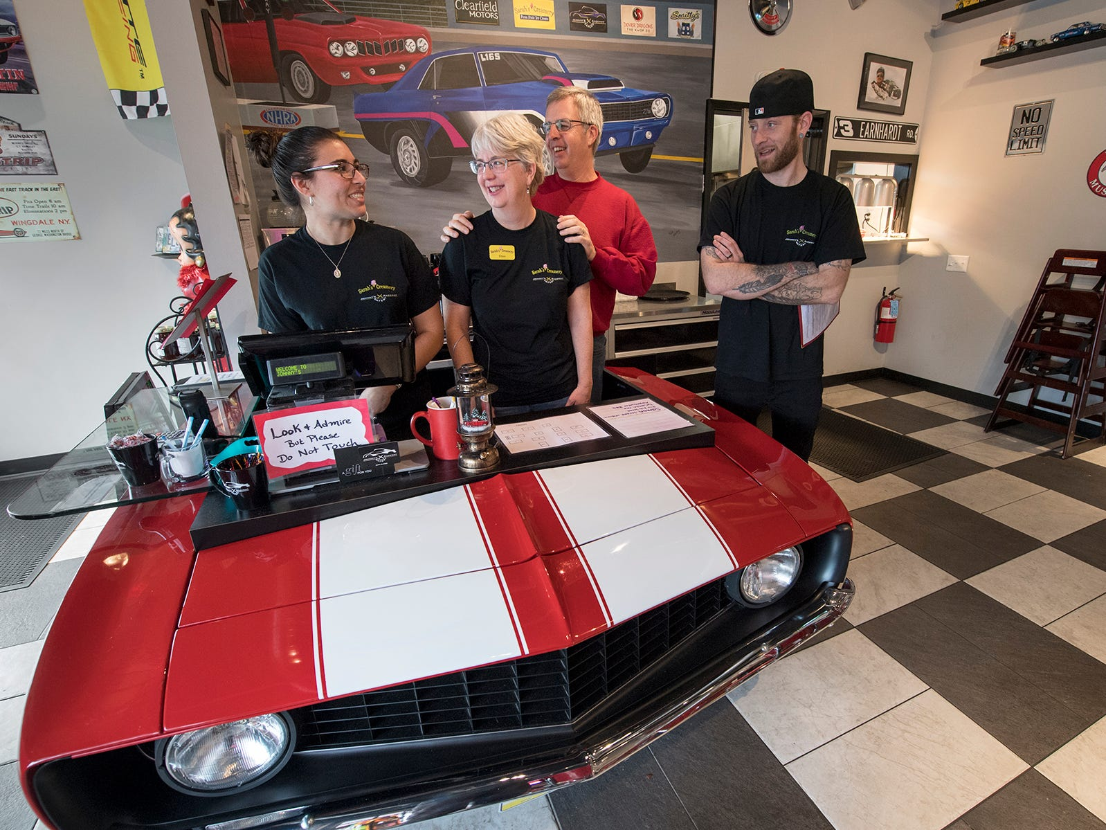 From the left, Carly Rossi, Ellen Shaffer, Jerry Shaffer, and Matt Burnham in front of the register desk that is modeled after a 69 Camaro. Jerry Shaffer made the desk out of reproduction parts and a hood from an actual Camaro.