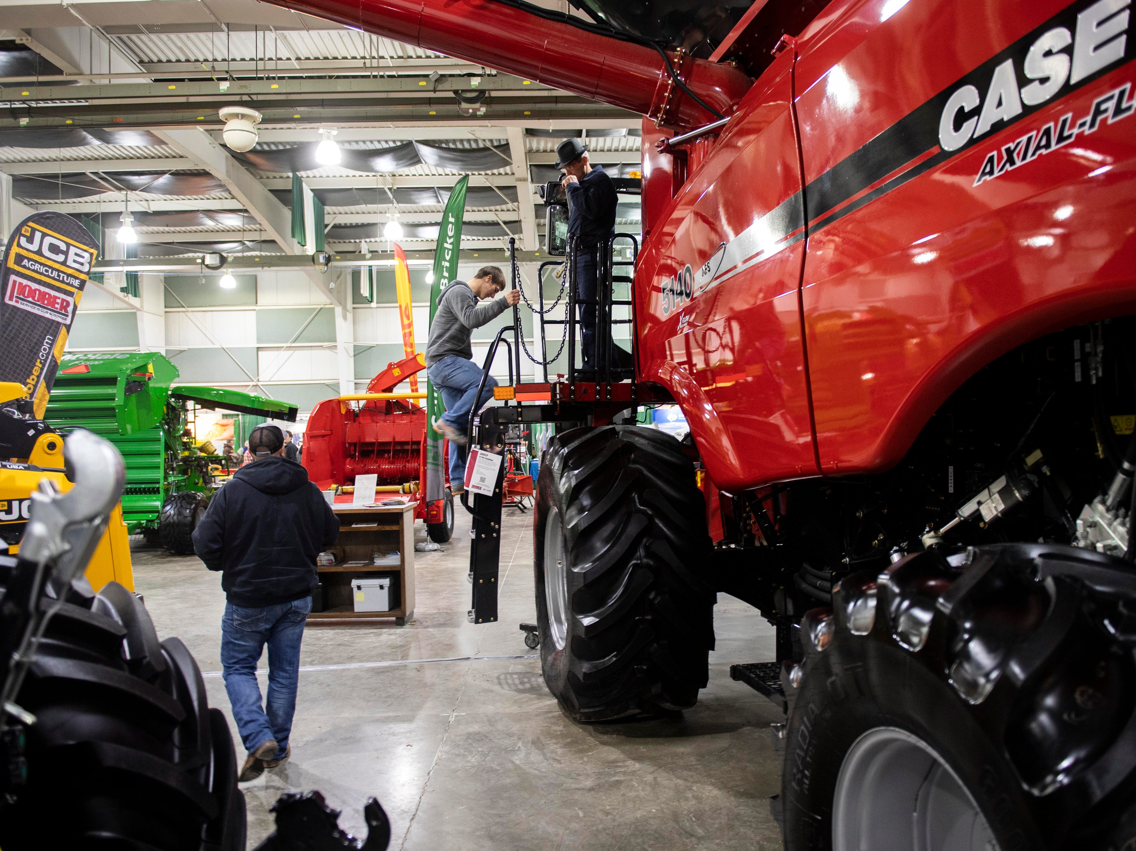 A man climbs down after checking out the inside of a combine, Tuesday, Jan. 8, 2019. The Keystone Farm Show has nearly 420 vendors and is expected to bring up to 15,000 people to the York Expo Center. The show runs through Thursday, Jan. 10.