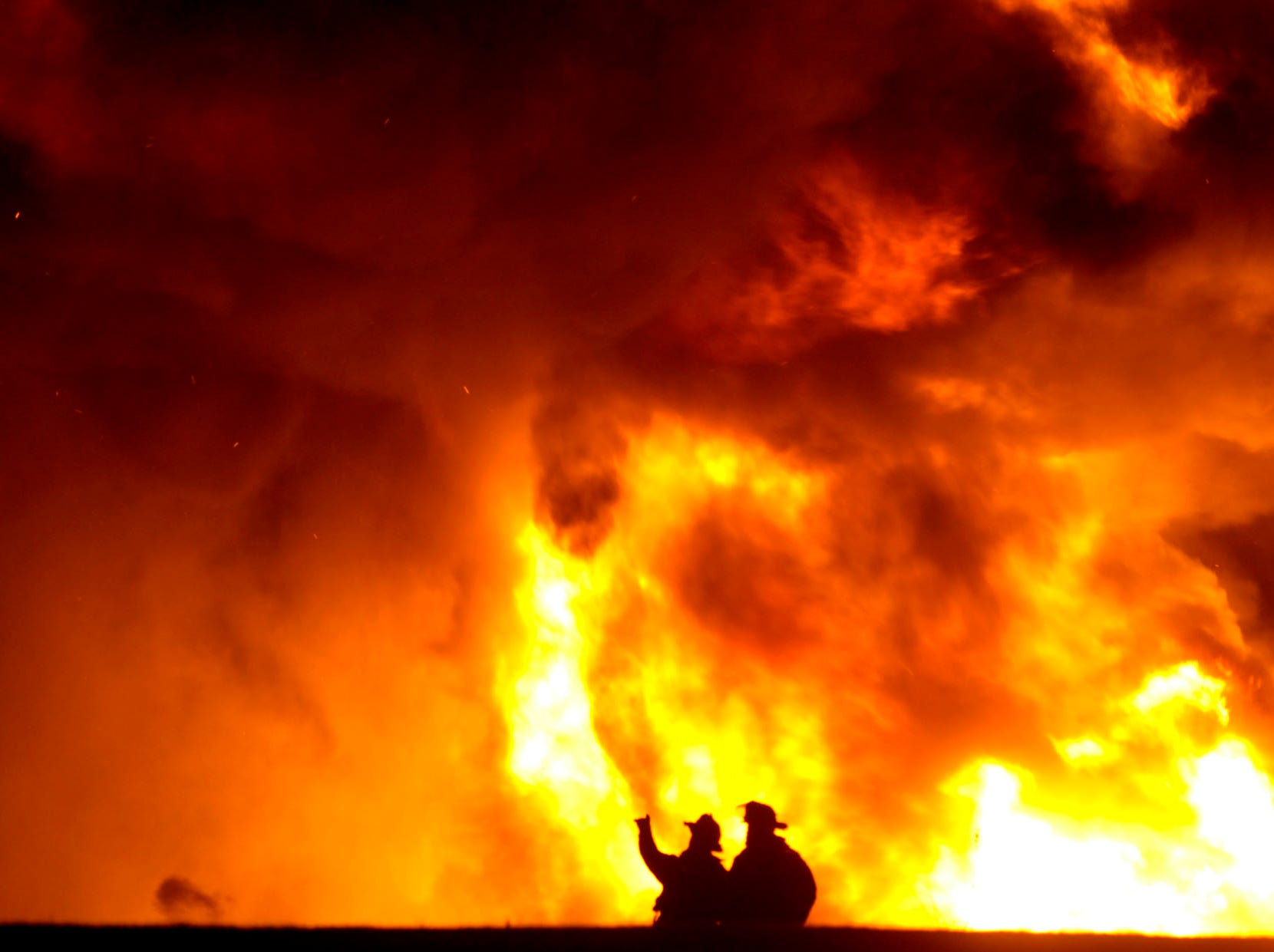 Fire fighters are dwarfed by multiple explosions from a four alarm fire at Adhesives Research, Inc. January 10, 2006.