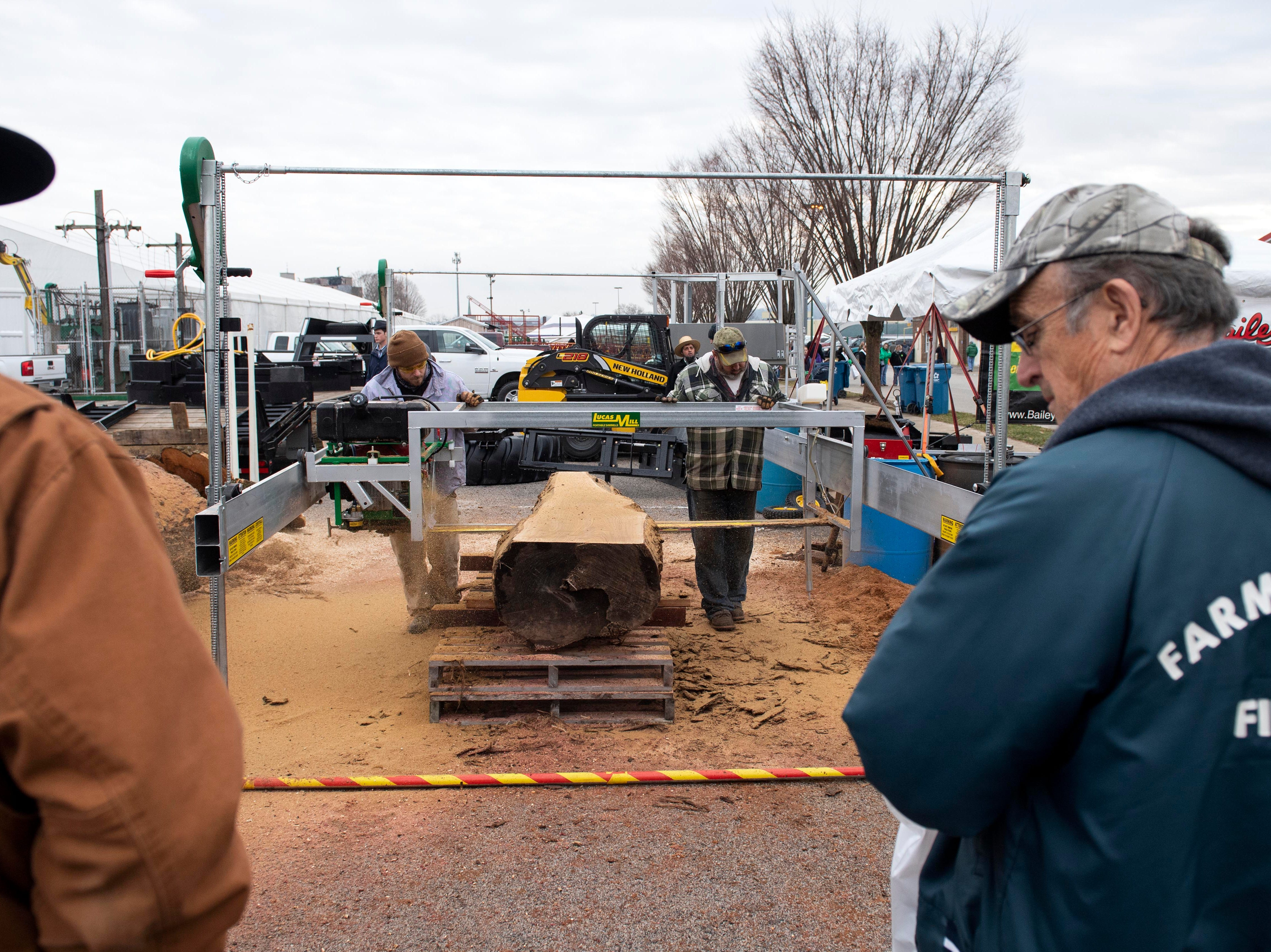 Bystanders watch a demonstration of a portable saw system, Tuesday, Jan. 8, 2019. The Keystone Farm Show has nearly 420 vendors and is expected to bring up to 15,000 people to the York Expo Center. The show runs through Thursday, Jan. 10.