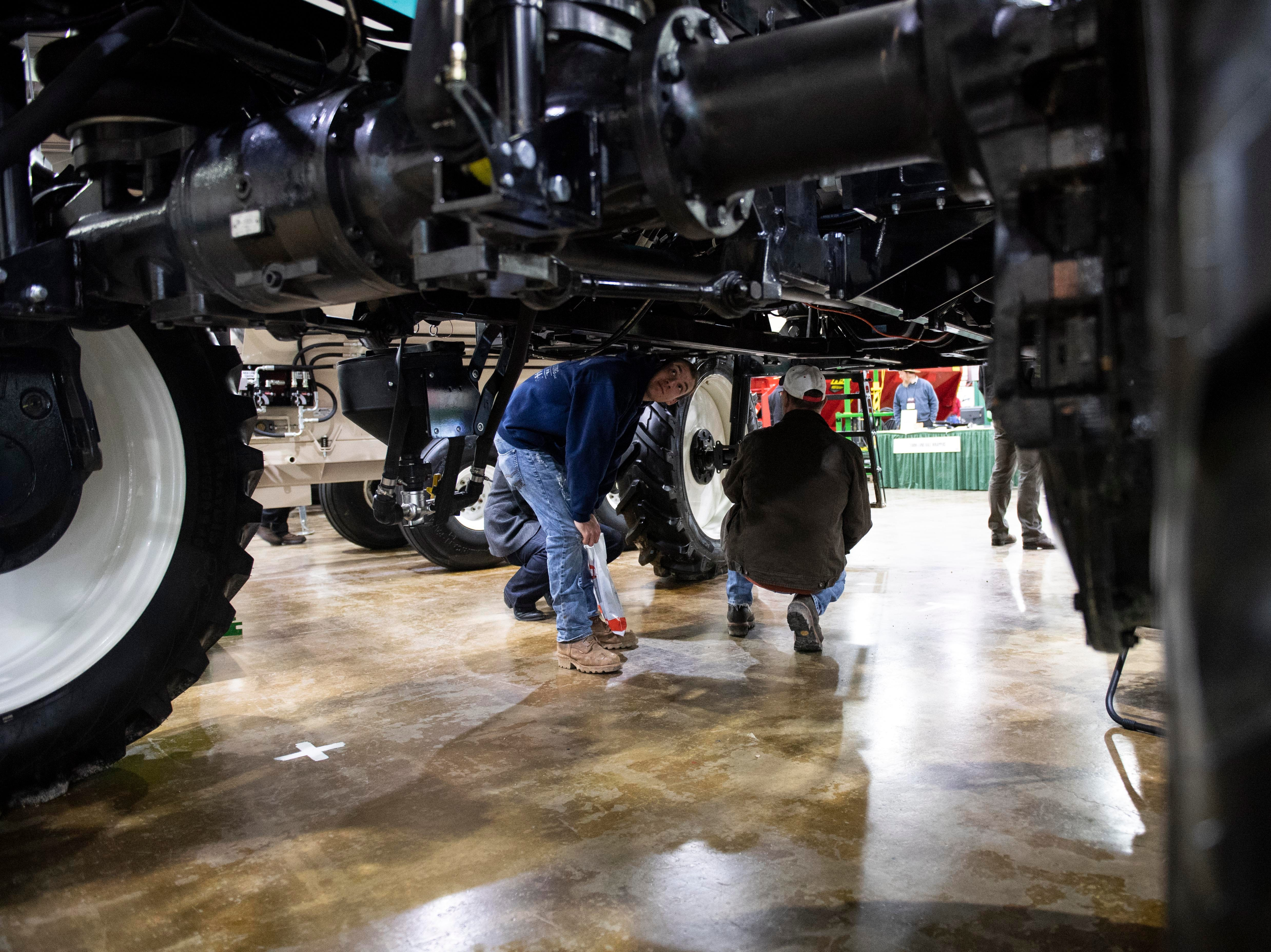 Folks attending the Keystone Farm Show look over the underside of a sprayer, Tuesday, Jan. 8, 2019. The Keystone Farm Show has nearly 420 vendors and is expected to bring up to 15,000 people to the York Expo Center. The show runs through Thursday, Jan. 10.