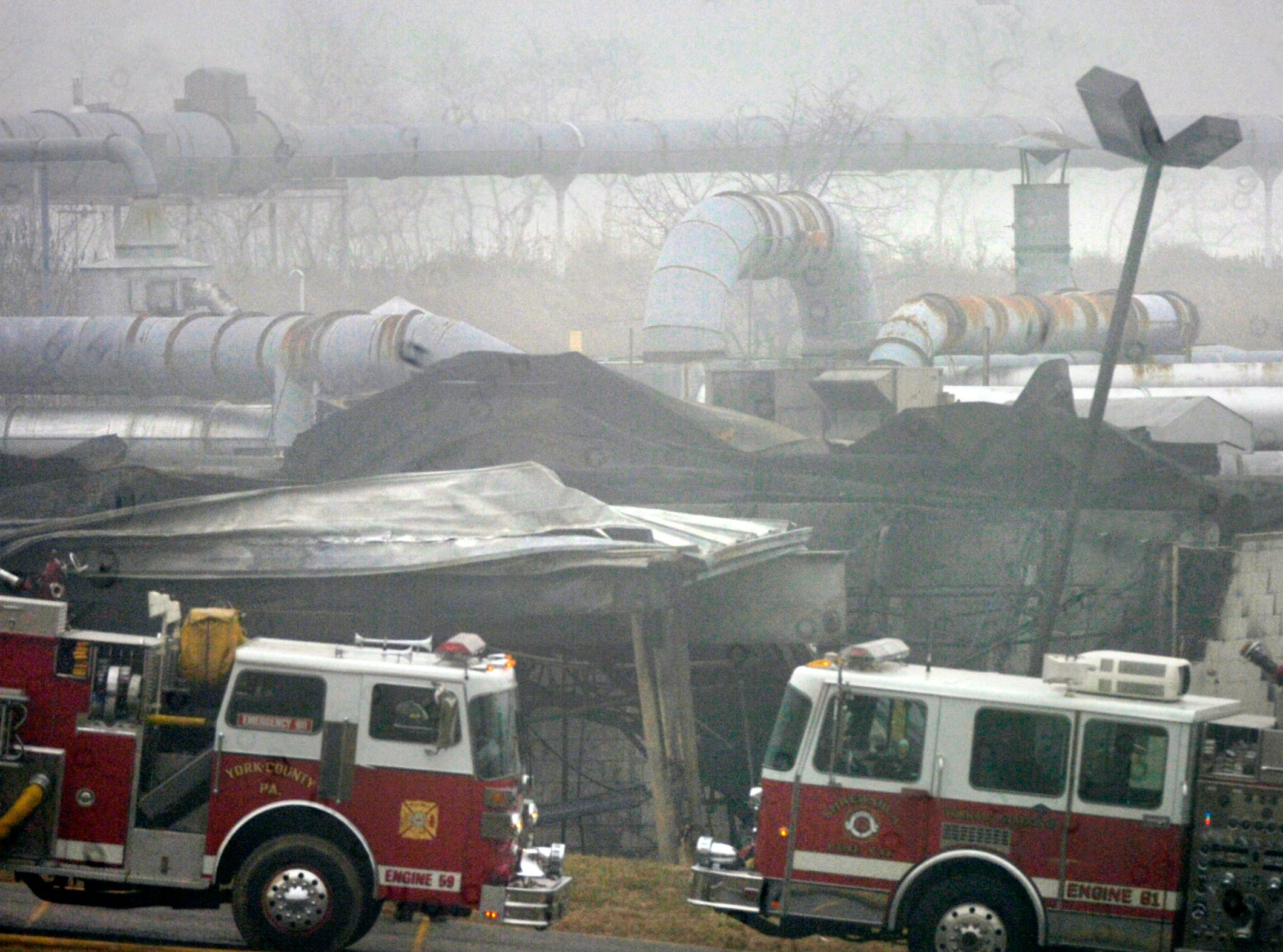 Fire trucks line the front of the damaged storage facility of Adhesives Research in Springfield Township after the fire on January 11, 2006.