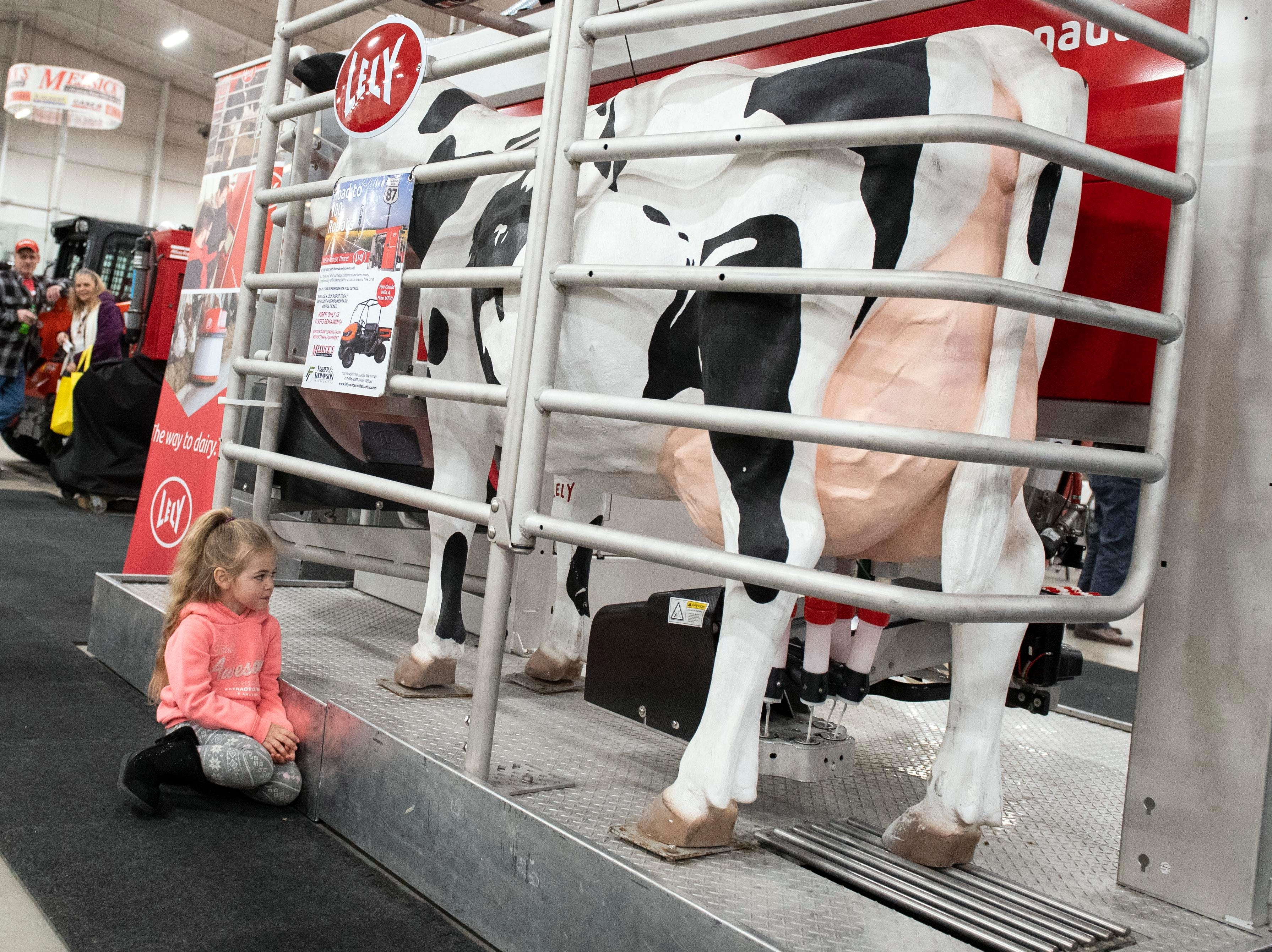 A little girl watches as a simulation demonstrates how a robotic milking machine works, Tuesday, Jan. 8, 2019. The Keystone Farm Show has nearly 420 vendors and is expected to bring up to 15,000 people to the York Expo Center. The show runs through Thursday, Jan. 10.