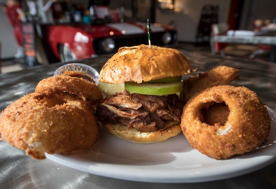 The Indy 500 is a boneless rib sandwich with dry rub, slow roasted in apple butter BBQ with served on an Brioche Onion bun with sliced Granny Smith apples on top. The sandwich is surrounded by onion rings at Johnny's Raceway Eatery Tuesday January 8, 2019.
