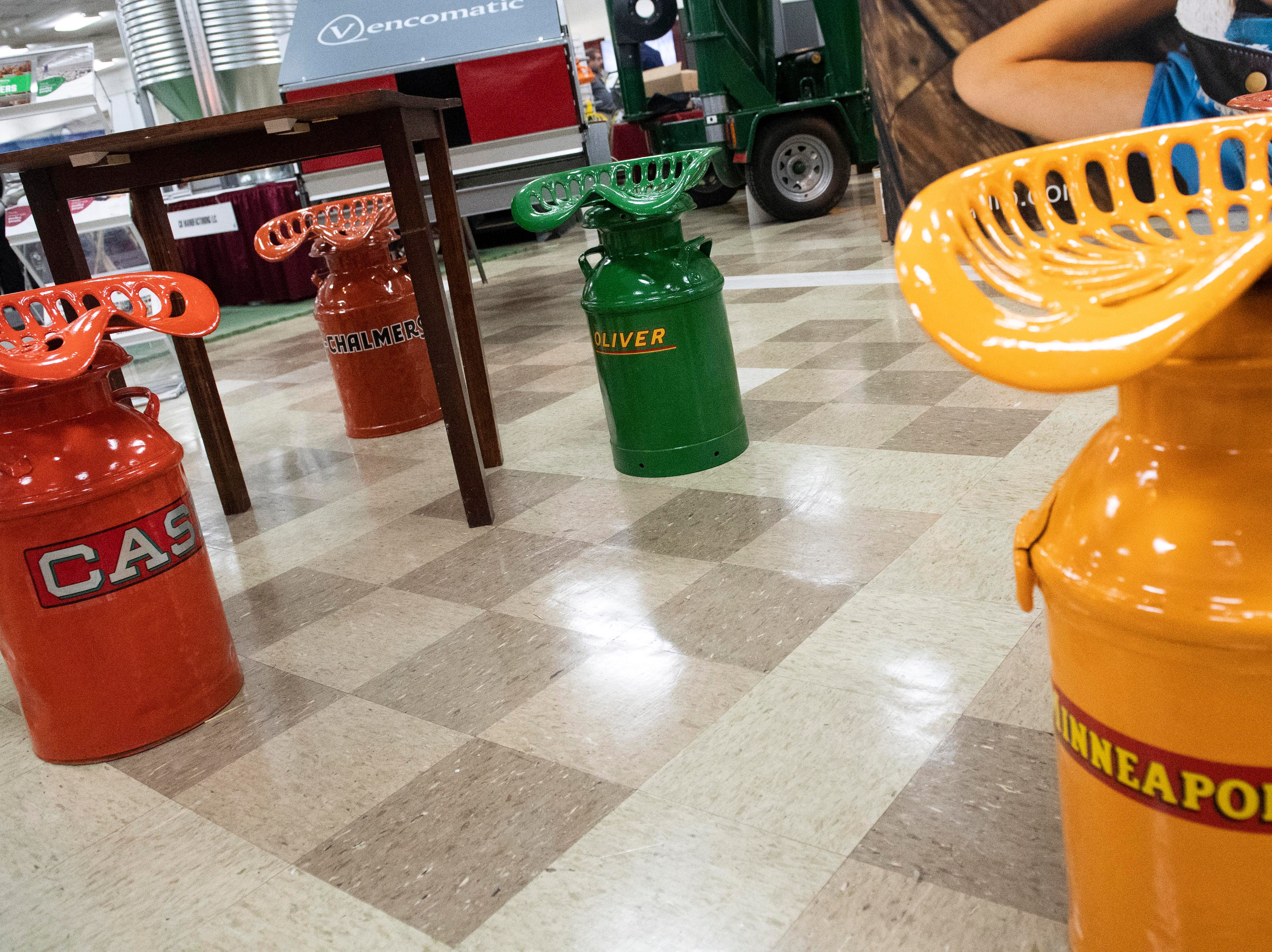 Custom milk-jug tractor seats sit around tables at a vendor's booth on Tuesday, Jan. 8, 2019. The Keystone Farm Show has nearly 420 vendors and is expected to bring up to 15,000 people to the York Expo Center. The show runs through Thursday, Jan. 10.