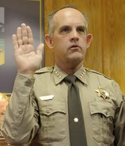 Lyon County Sheriff Frank Hunewill raises his right hand to take the oath.