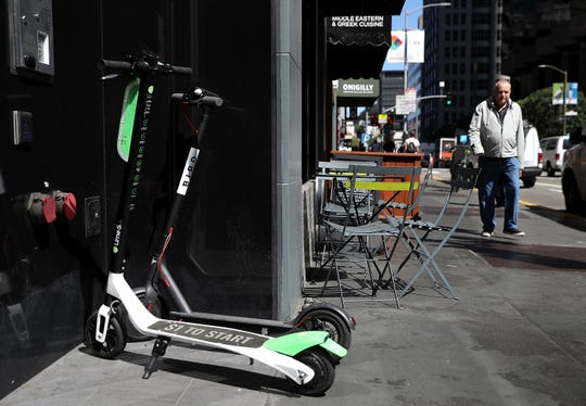 Bird and Lime scooters sit parked in front of a building on April 17, 2018 in San Francisco, California.