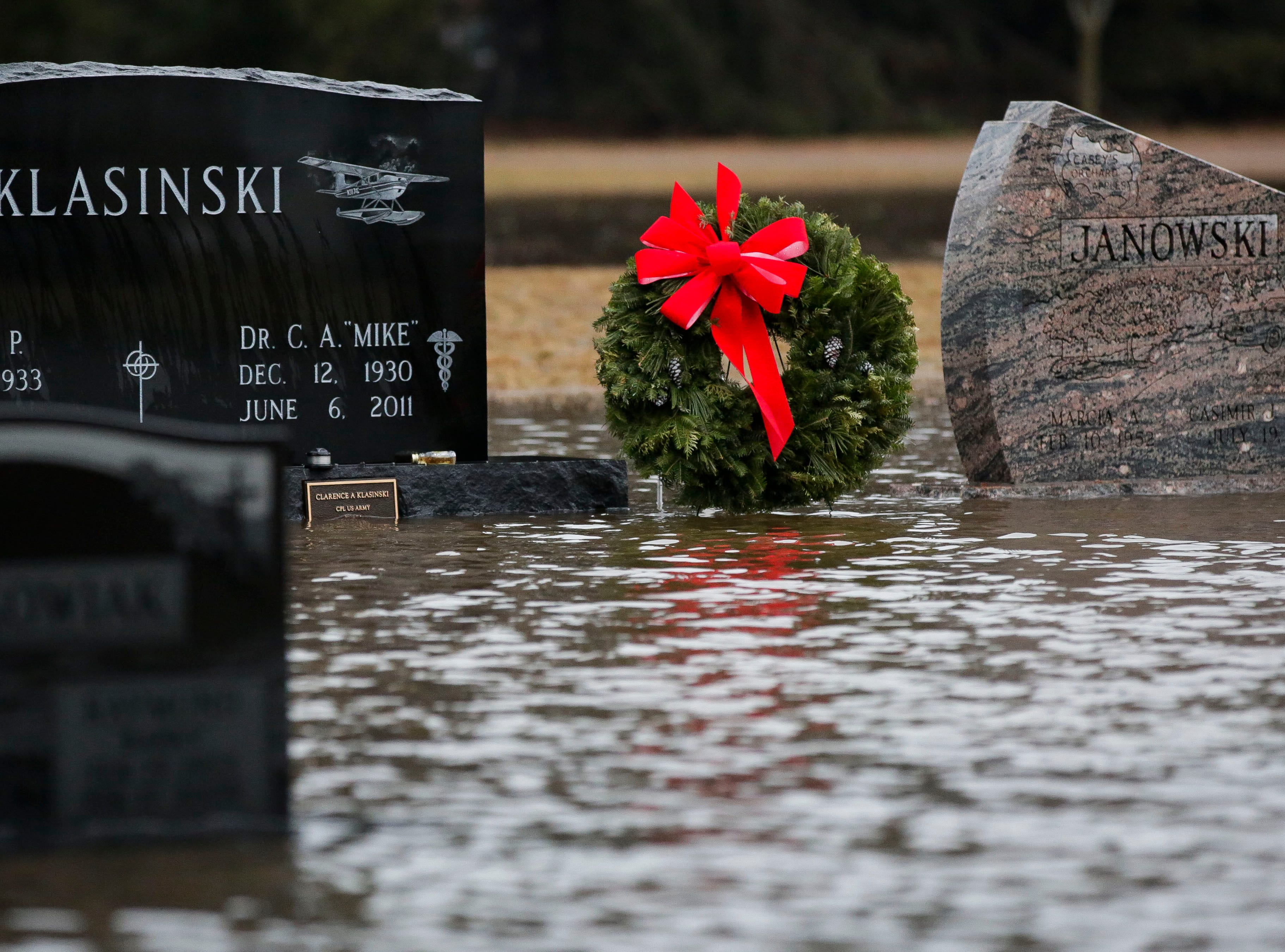 A wreath lays among headstones and flood waters  on Monday, January 7, 2019, at Guardian Angel Cemetery in Stevens Point, Wis. Tork Mason/USA TODAY NETWORK-Wisconsin