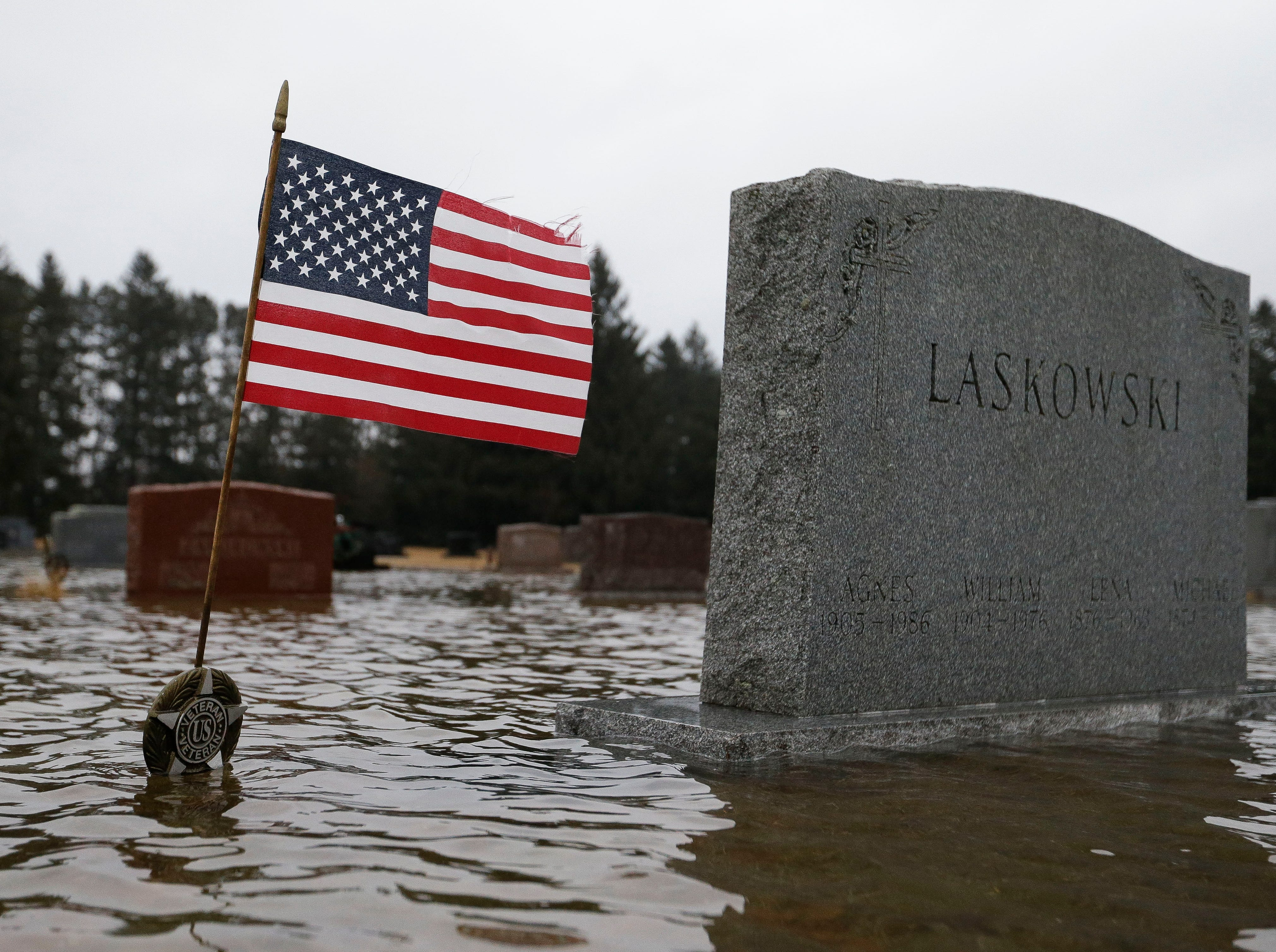 An American Flag waves above flood waters on Monday, January 7, 2019, at Guardian Angel Cemetery in Stevens Point, Wis. Tork Mason/USA TODAY NETWORK-Wisconsin