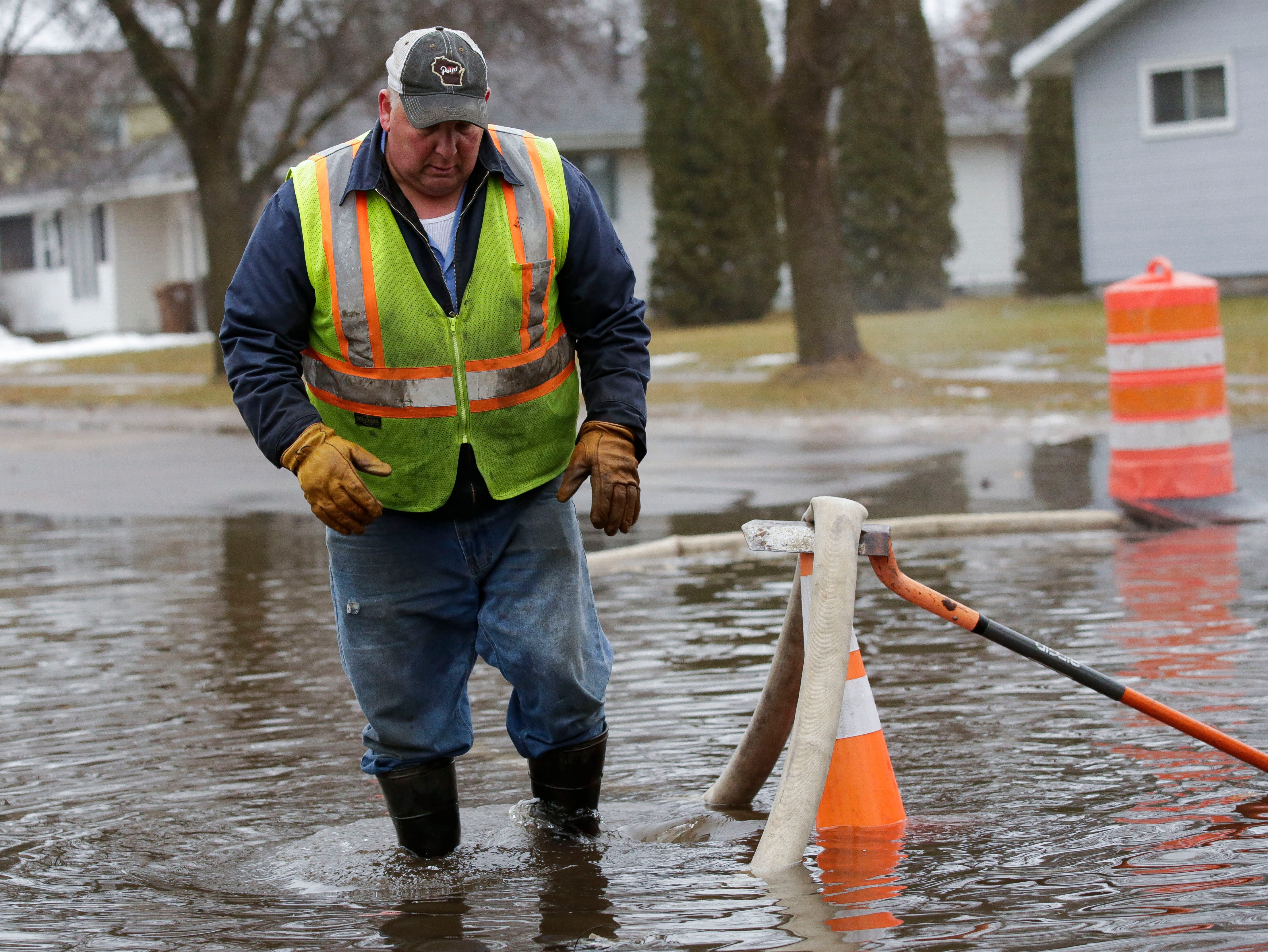 Stevens Point utlities worker Tony Sterling pumps flood water on Monday, January 7, 2019, at the intersection of Soo Marie Avenue and Rice Street in Stevens Point, Wis.Tork Mason/USA TODAY NETWORK-Wisconsin
