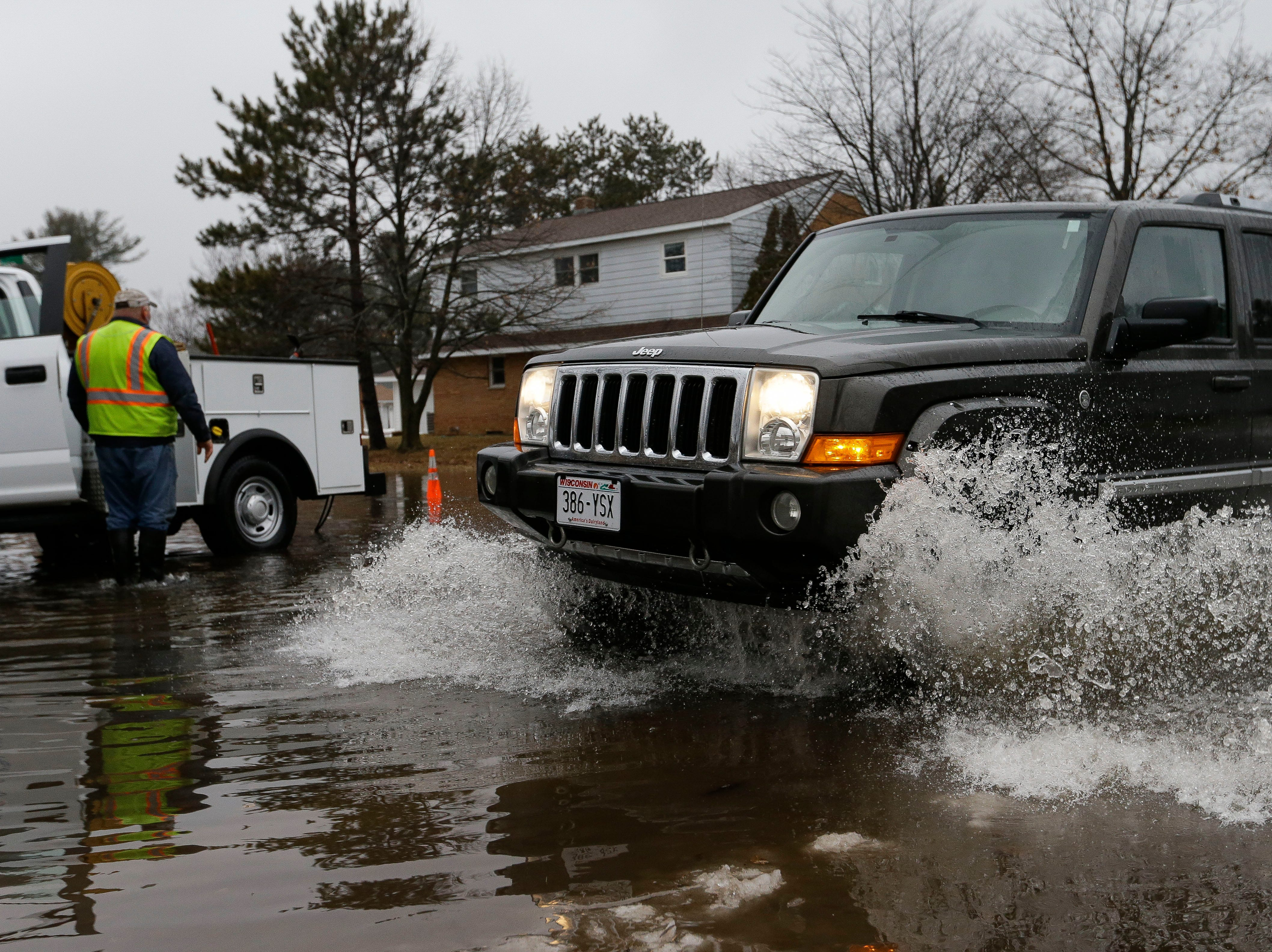 A car drives through the flooded intersection of Soo Marie Avenue and Rice Street on Monday, January 7, 2019, in Stevens Point, Wis.Tork Mason/USA TODAY NETWORK-Wisconsin