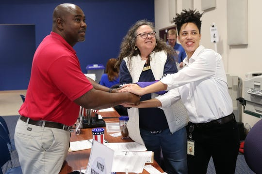 The Supervisor of Elections office has constant foot-traffic on Tuesday, Jan. 8, 2019, as Amendment 4 is now in effect. The Amendment restored the right to vote for felons not convicted on sex offenses or murder. Delmus Calloway, left, shakes hands with Susie Caplowe, outreach specialist for the Supervisor of Elections office, and Monique Duncan-Jones, outreach manager at the Supervisor of Elections office. Calloway had just finished registering to vote.