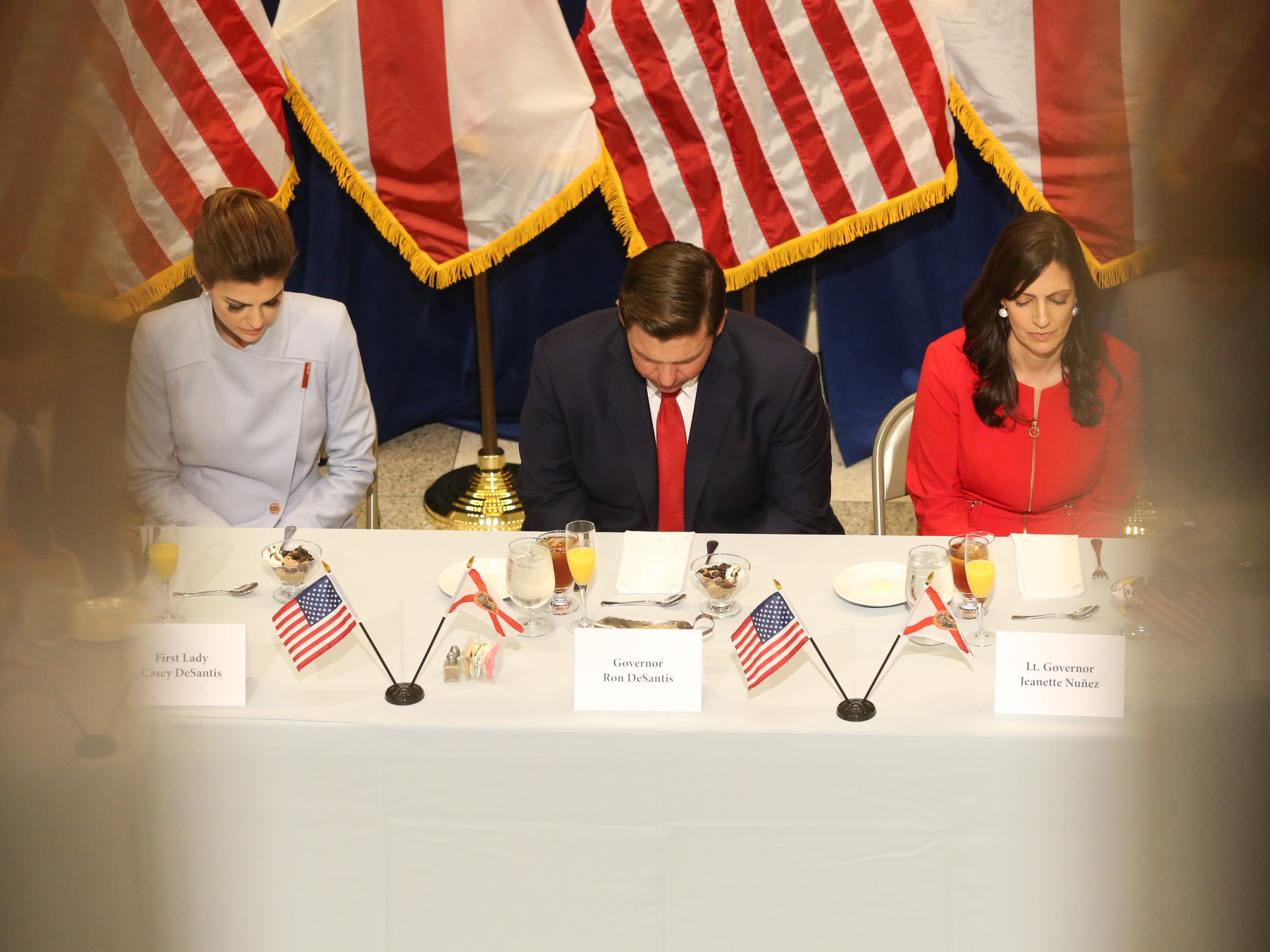 For the first time in Inaugural history, Gov. Ron DeSantis addresses FloridaÕs Legislative leaders and Cabinet officials. DeSantis discusses his plans to work with our stateÕs elected leaders to achieve a Bold Vision for a Brighter Future, Tuesday, Jan. 8, 2019. First lady Casey DeSantis, left, Gov. Ron DeSantis, and Lt. Gov. Jeanette Nunez, bow their heads as a prayer is said before the luncheon.