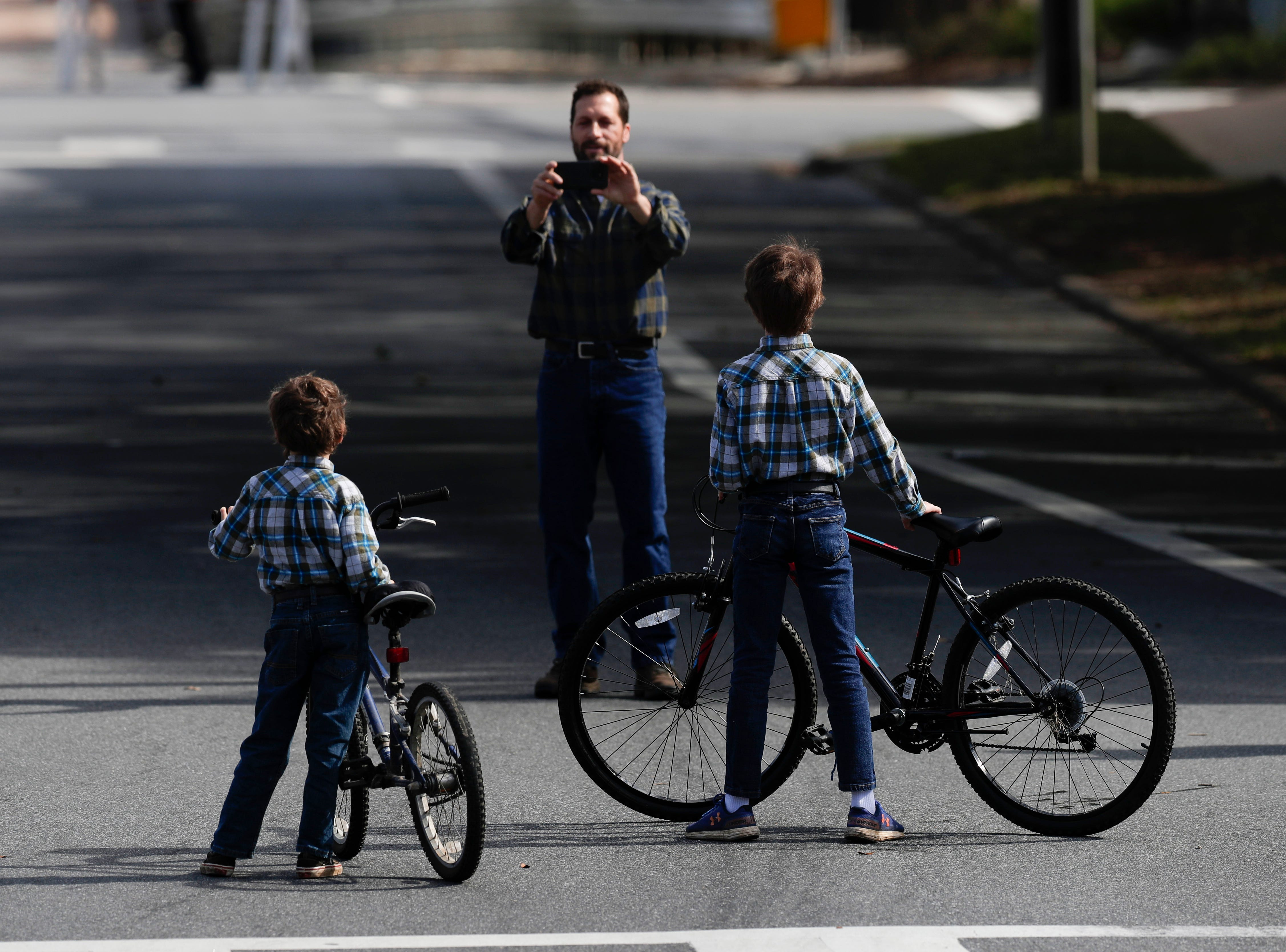 A man takes a photo of his two sons in front of the Historic Capitol after the 2019 inauguration ceremony on the steps of the Historic Capitol Building in Tallahassee Tuesday, Jan. 8, 2019.