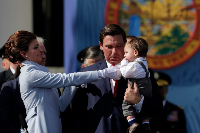First lady Casey DeSantis takes Gov. Ron DeSantis' lavalier microphone out of their son Mason's mouth after the governor gave his inaugural speech during the 2019 inauguration ceremony on the steps of the Historic Capitol Building in Tallahassee Tuesday, Jan. 8, 2019.