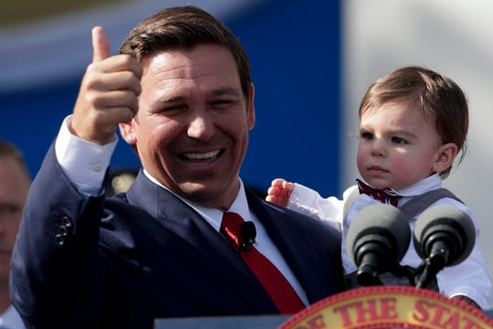 Gov. Ron DeSantis, holding his son Mason DeSantis, gives a thumbs up to the crowd after giving his inaugural speech during the 2019 inauguration ceremony on the steps of the Historic Capitol Building in Tallahassee Tuesday, Jan. 8, 2019.