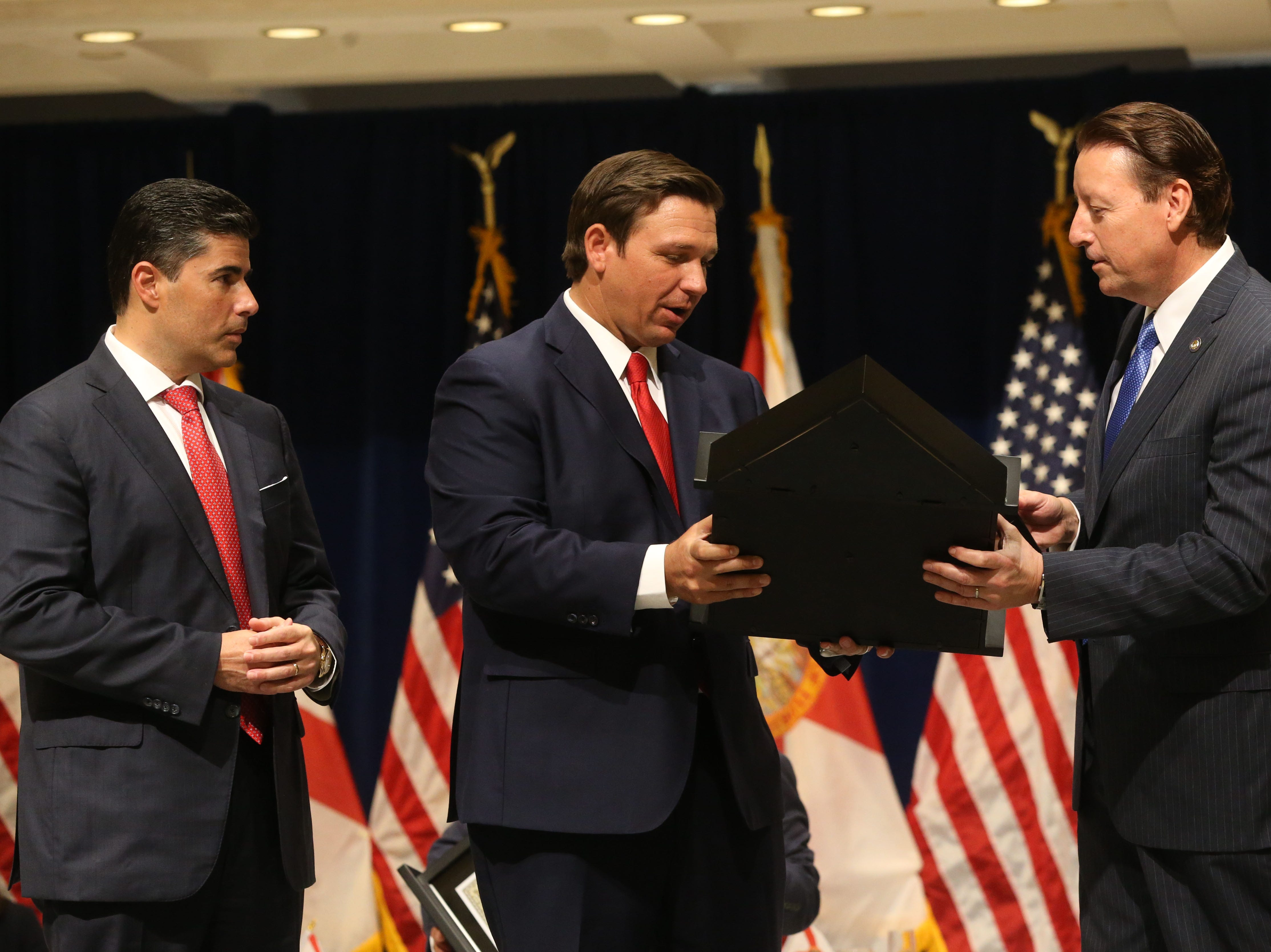 For the first time in Inaugural history, Gov. Ron DeSantis addresses FloridaÕs Legislative leaders and Cabinet officials. DeSantis discusses his plans to work with our stateÕs elected leaders to achieve a Bold Vision for a Brighter Future, Tuesday, Jan. 8, 2019. Gov. Ron DeSantis, center, gives a flag that was flown during the inauguration earlier in the morning to Senate President Bill Galvano, right, and House Speaker Jose Oliva, left.