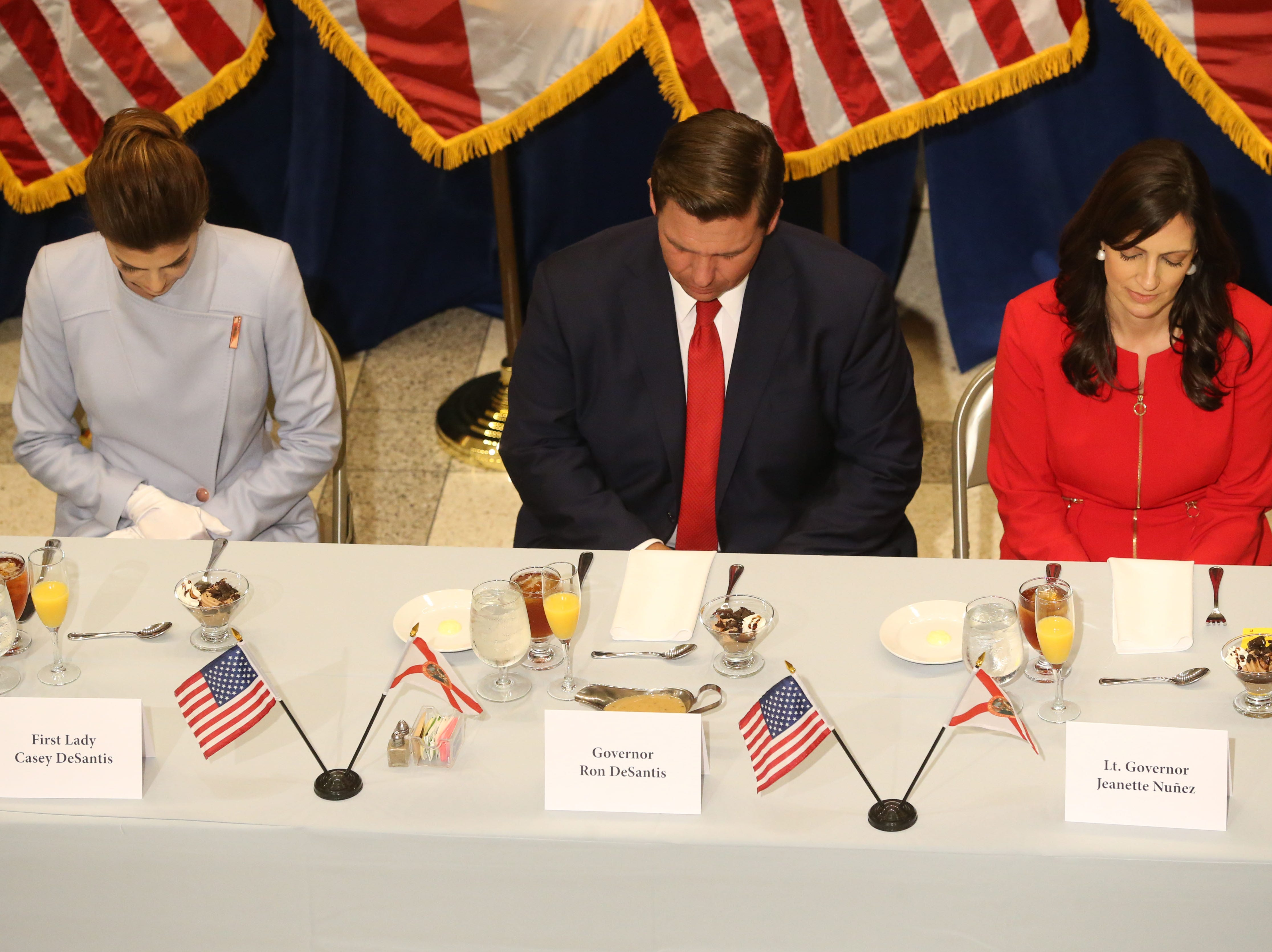 For the first time in Inaugural history, Gov. Ron DeSantis addresses FloridaÕs Legislative leaders and Cabinet officials. DeSantis discusses his plans to work with our stateÕs elected leaders to achieve a Bold Vision for a Brighter Future, Tuesday, Jan. 8, 2019. First lady Casey DeSantis, left, Gov. Ron DeSantis, and Lt. Gov. Jeanette Nunez bow their head in prayer before lunch.