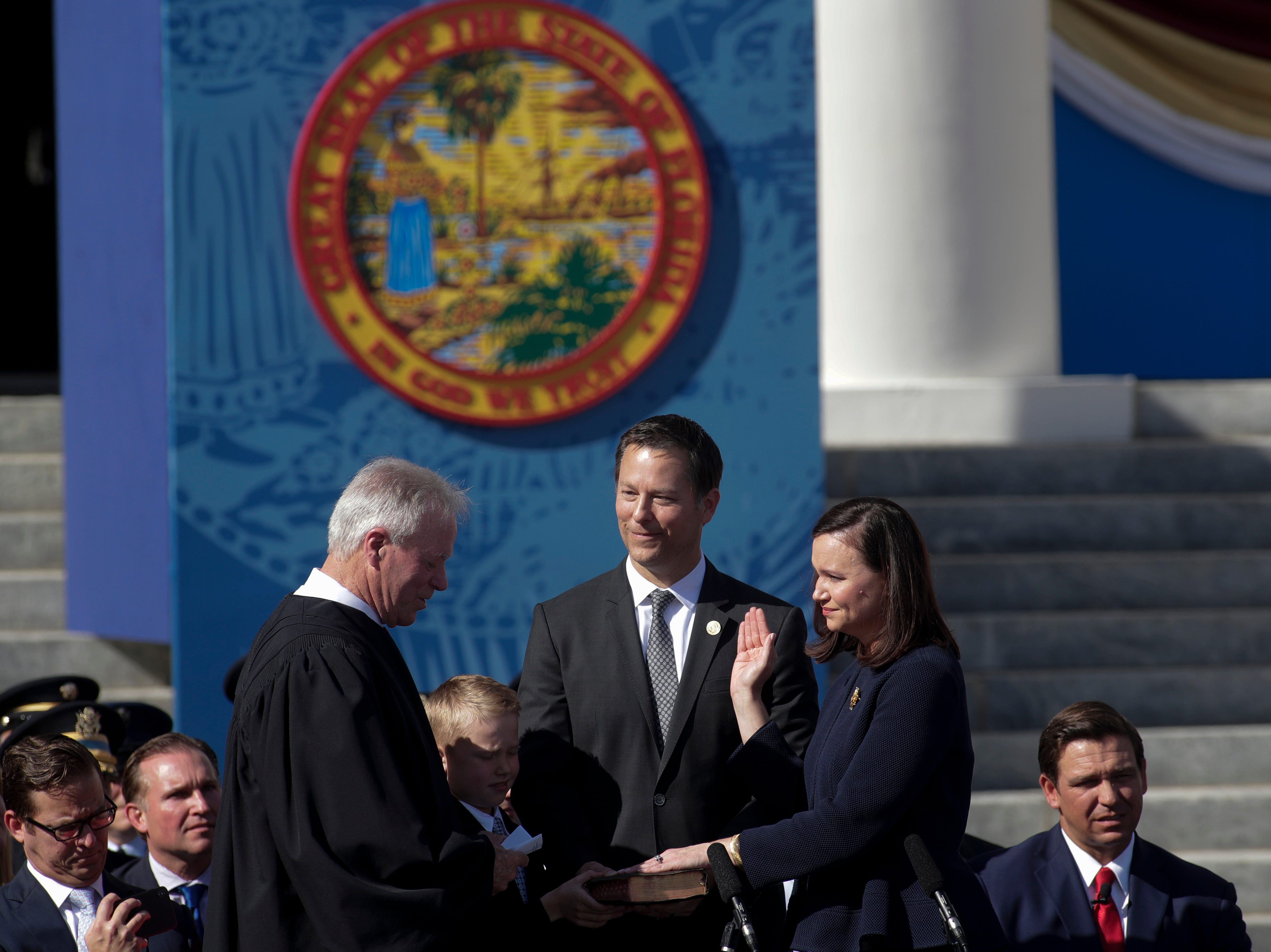 Attorney General Ashley Moody takes the oath of office administered by her father Judge James S. Moody with her husband Justin Duralia and their son Connor Duralia during the 2019 inauguration ceremony on the steps of the Historic Capitol Building in Tallahassee Tuesday, Jan. 8, 2019.