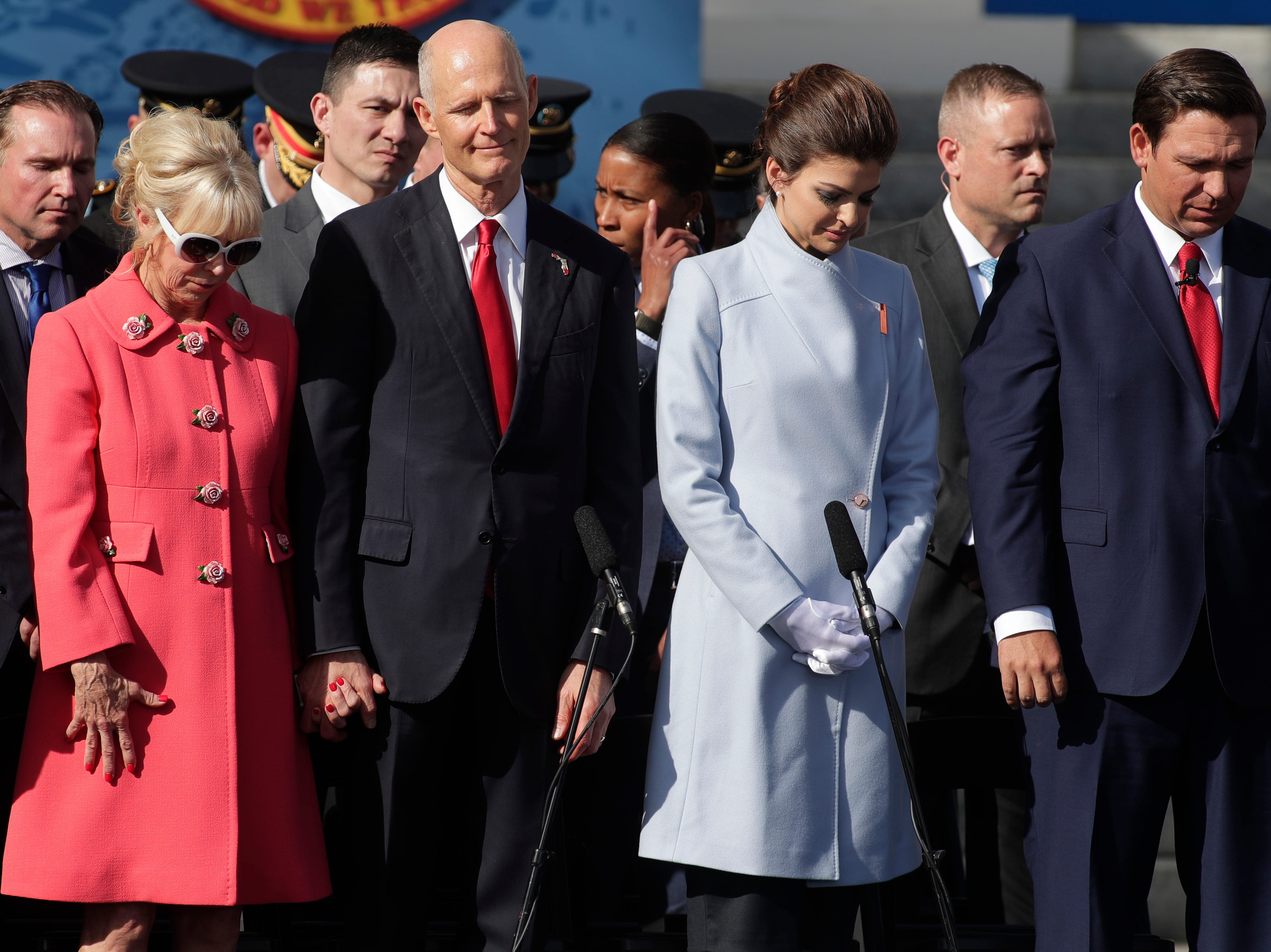 Former first lady Ann Scott, former governor Rick Scott, first lady Casey DeSantis and Gov. Ron DeSantis bow their heads during an invocation by Rev. Gary Johnson during the 2019 inauguration ceremony on the steps of the Historic Capitol Building in Tallahassee Tuesday, Jan. 8, 2019.