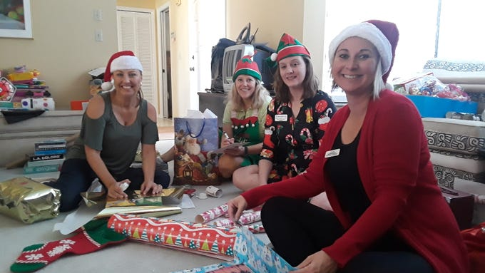 Martin County Santa's Elves, from left, Heidi Monsour, Ellen Houts, Ashley Braden-Knowles and Michelle Schwartz hard at work wrapping gifts for all the children living at the Jensen Beach Shelter.