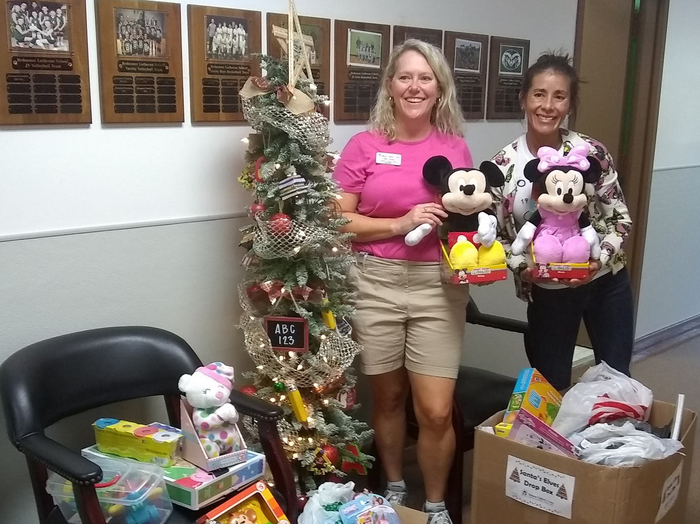 The kindergarten and first grade classes of Redeemer Lutheran School donated lots of wonderful toys for the Jensen Beach Shelter. Santa's Elves Chair Ellen Houts, left, was delighted to receive the gifts from Angie Jones at Redeemer.