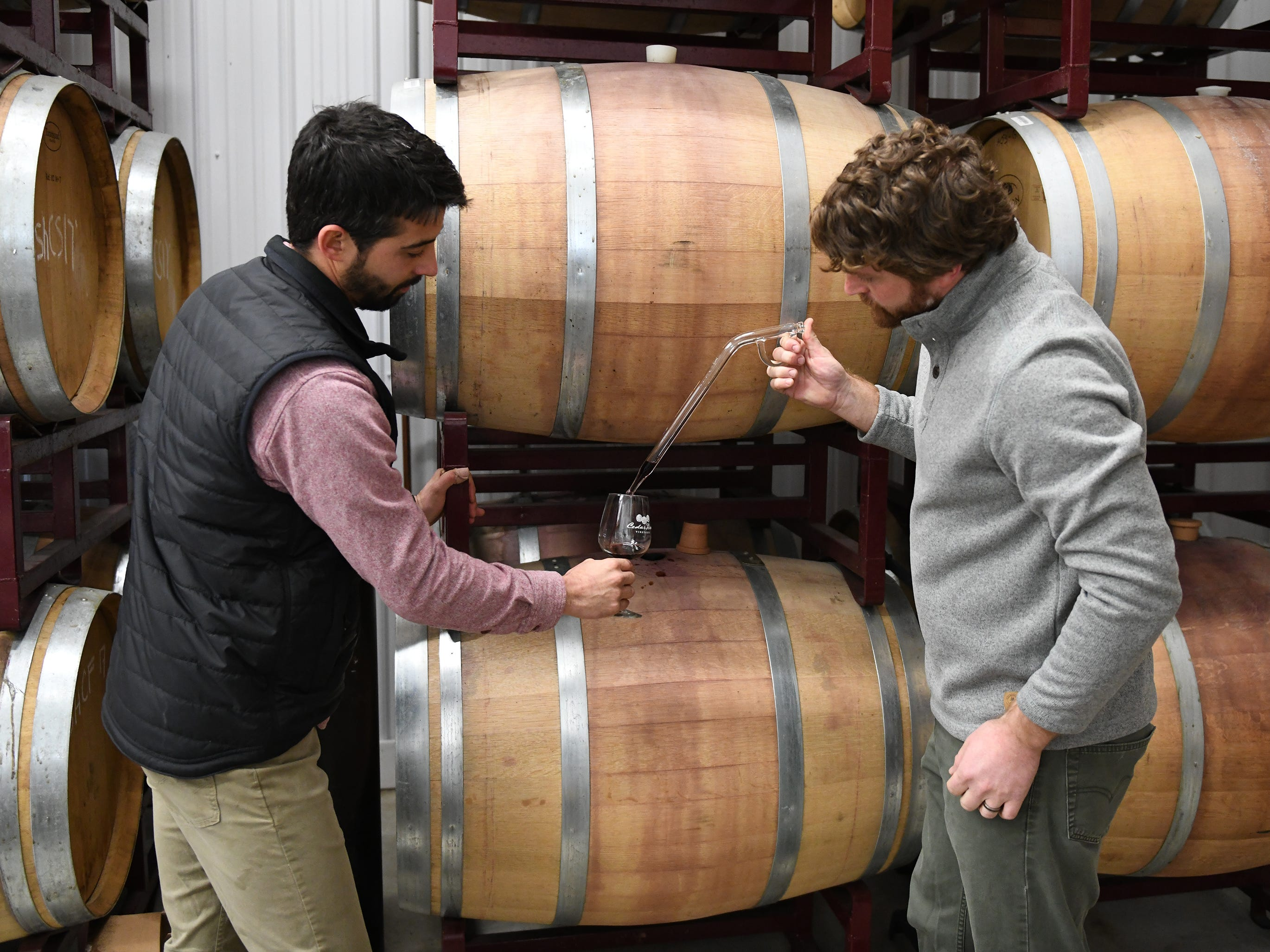 Cedar Rose Vineyards managing partners Steven Becker (left) and Dustin Tarpine extract a barrel sample using a glass wine thief on Tuesday, January 8, 2019.