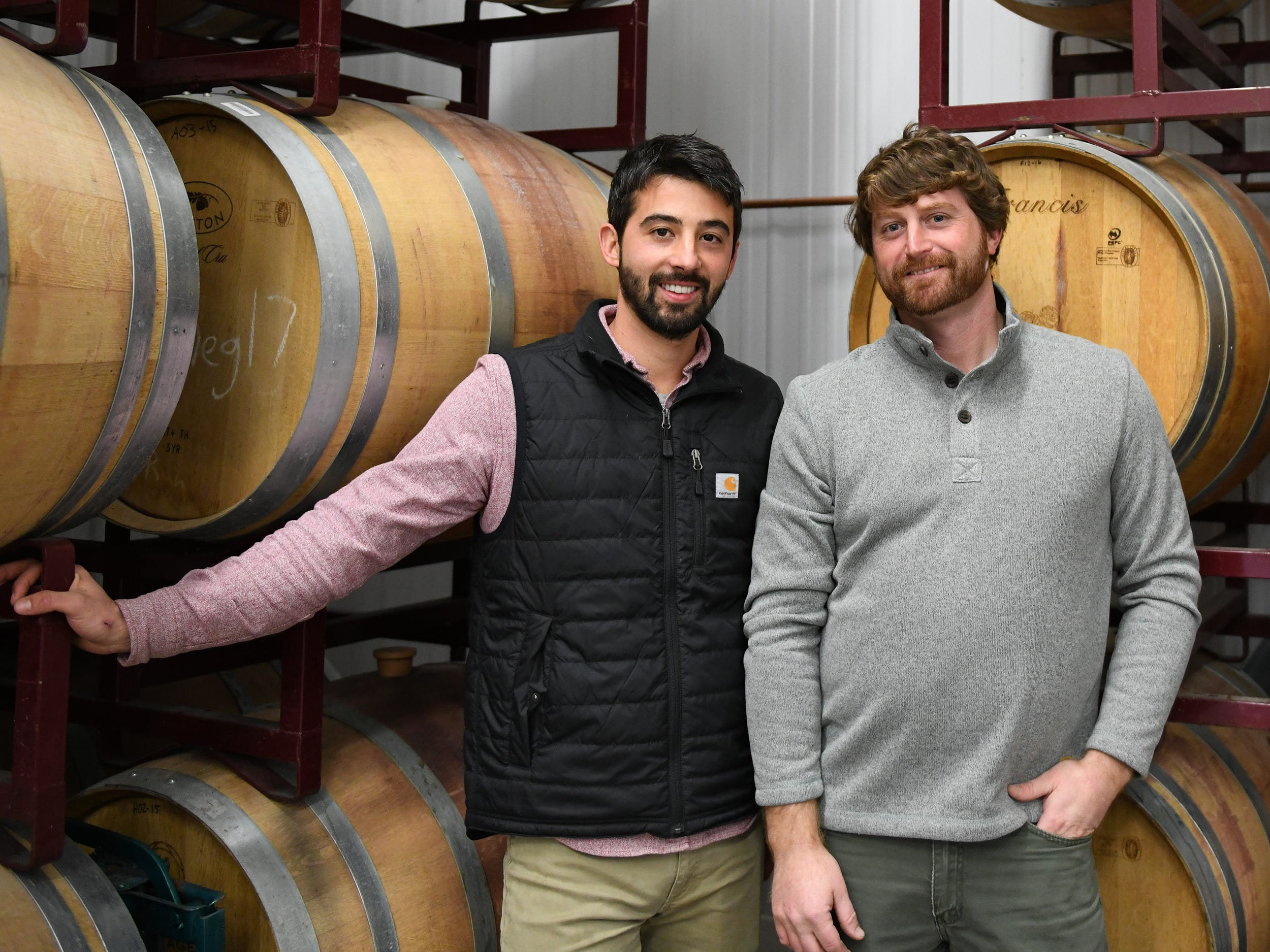 Cedar Rose Vineyards managing partners Steven Becker (left) and Dustin Tarpine stand next to barrels of wine produced at their Rosenhayn facility on Tuesday, January 8, 2019.