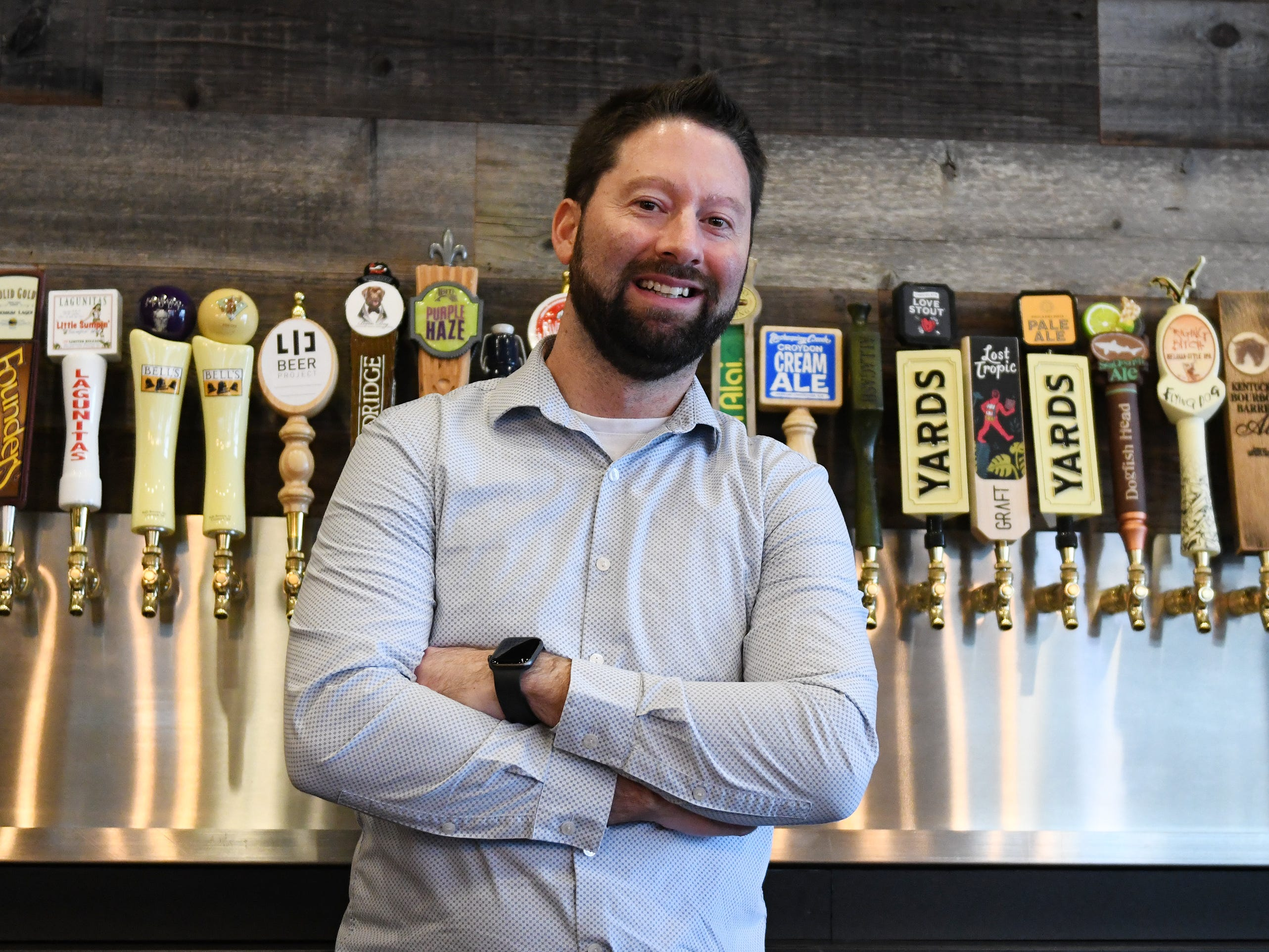 Chris Carmany, manager of The Brass Tap in Vineland, stands in front of a large selection of craft beers on Monday, Jan. 8. 2019.