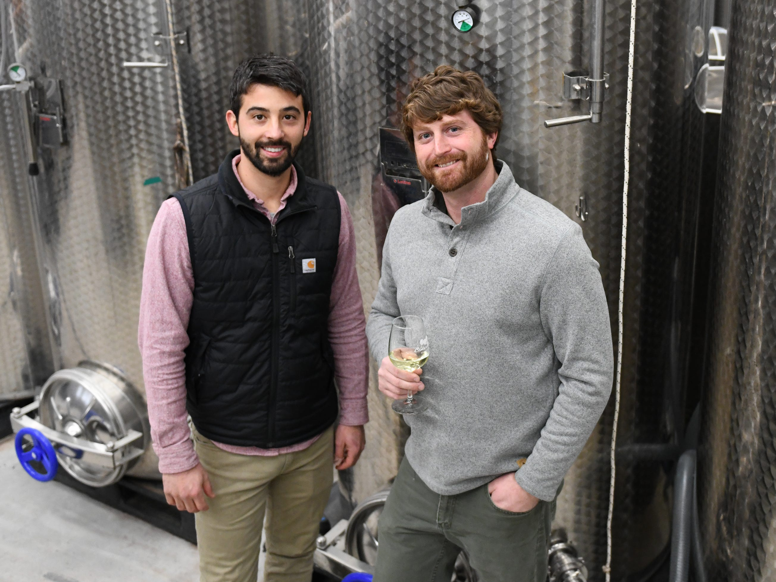 Cedar Rose Vineyards managing partners Steven Becker (left) and Dustin Tarpine stand next to stainless steel wine vats at their Rosenhayn facility on Tuesday, January 8, 2019.