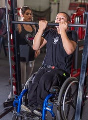 Trainer Becca Gonzales, left, watches Matthew Rodriguez, 13, pull up with his wheelchair at Grizz's Power House Gym in Tulare on Monday, January 7, 2019.