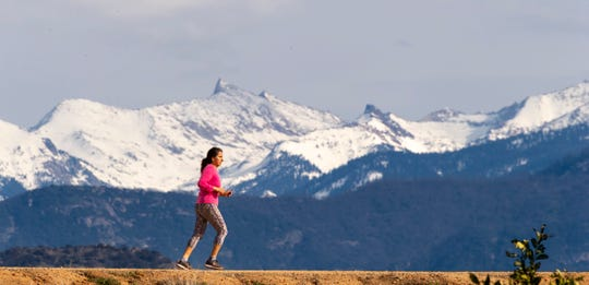 A snow-capped Sierra Mountain Range provides a scenic backdrop for a jogger on the perimeter of Bravo Lake in Woodlake on Tuesday, January 8, 2019.