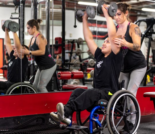 Trainer Becca Gonzales, right, spots Matthew Rodriguez, 13, with free weights at Grizz's Power House Gym in Tulare on Monday, January 7, 2019.