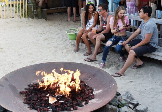 Bar-goers relax at northbeach's fire pit in May.
