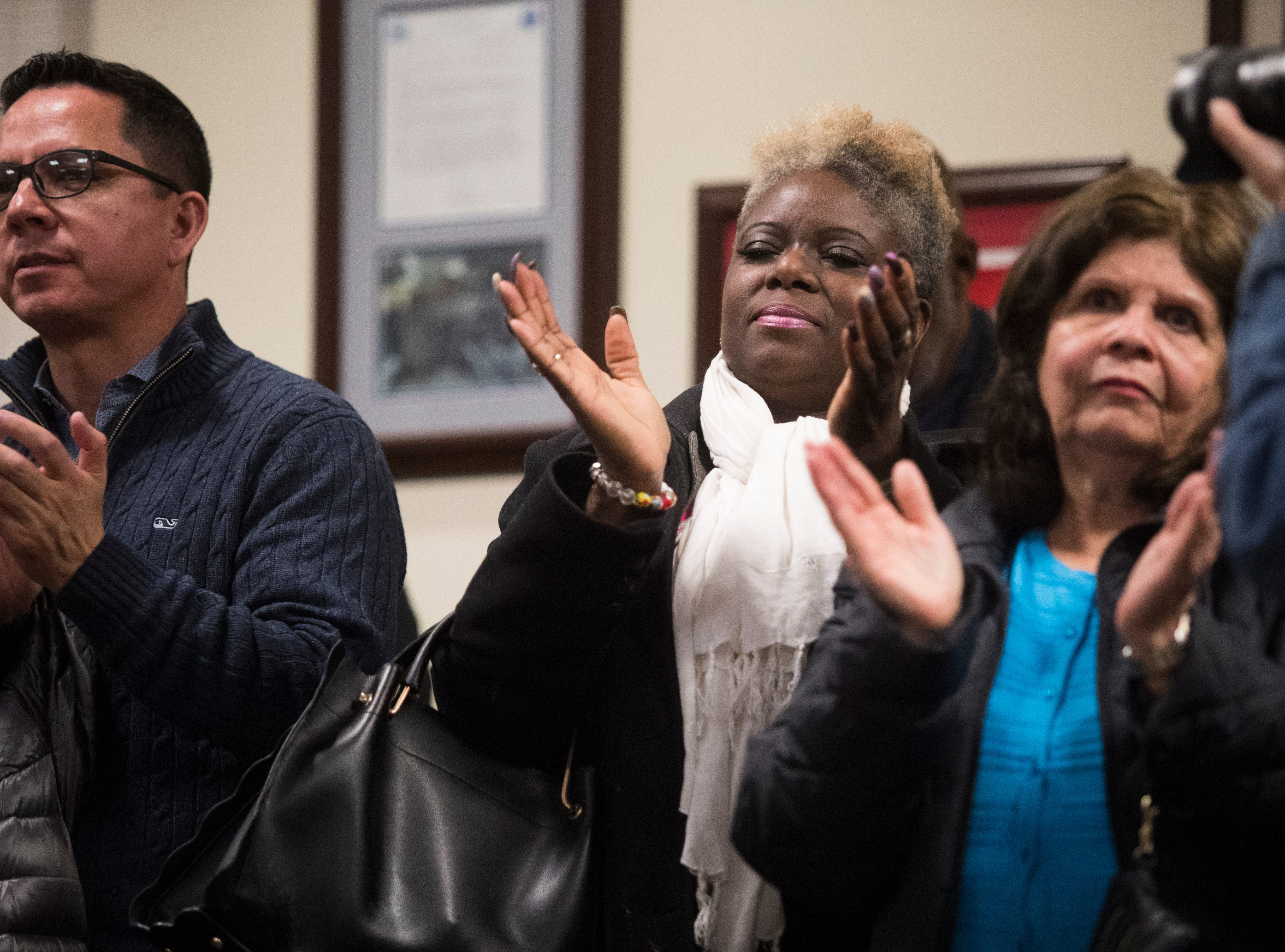 Members of the public clap as Kerri Evelyn Harris speaks to the Middletown City Council Monday night in Middletown.