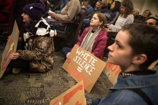 Jordan Resh, left, Katie Schoepp, center, and Rose Slavin hold signs protesting the recent Hummers Parade while sitting in the floor at a meeting of the Middletown City Council Monday night.