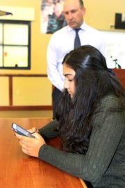 Appoquinimink High School junior Mehta Shreya loads the STOPit app onto her cell phone Monday as Tom Poehlmann, the district's director of safety, security and operations looks on. The district launched the app during an event Monday at the Appo High School library.