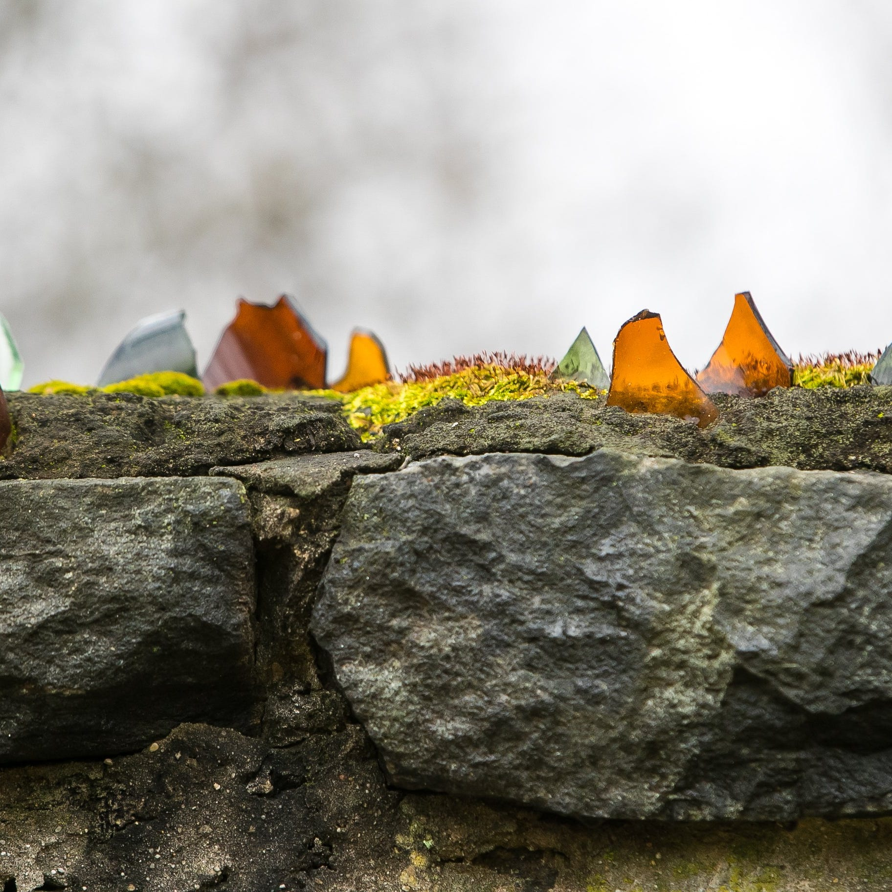Why does a duPont mansion have a stone wall topped with jagged glass shards?