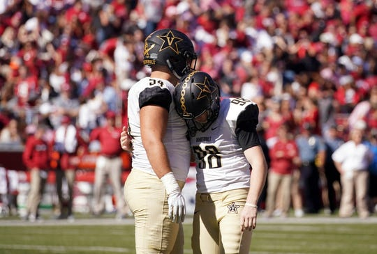 Vanderbilt's Kade Mayle (54, left) consoles kicker Ryley Guay (98) during a game during this past season.
