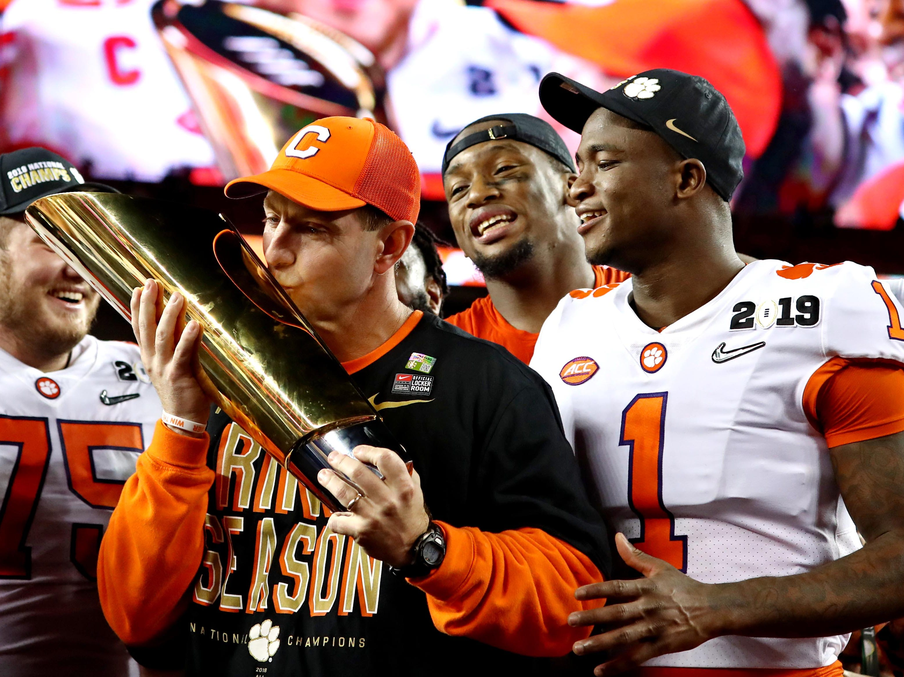 Clemson Tigers head coach Dabo Swinney celebrates with the national championship trophy after beating the Alabama Crimson Tide.