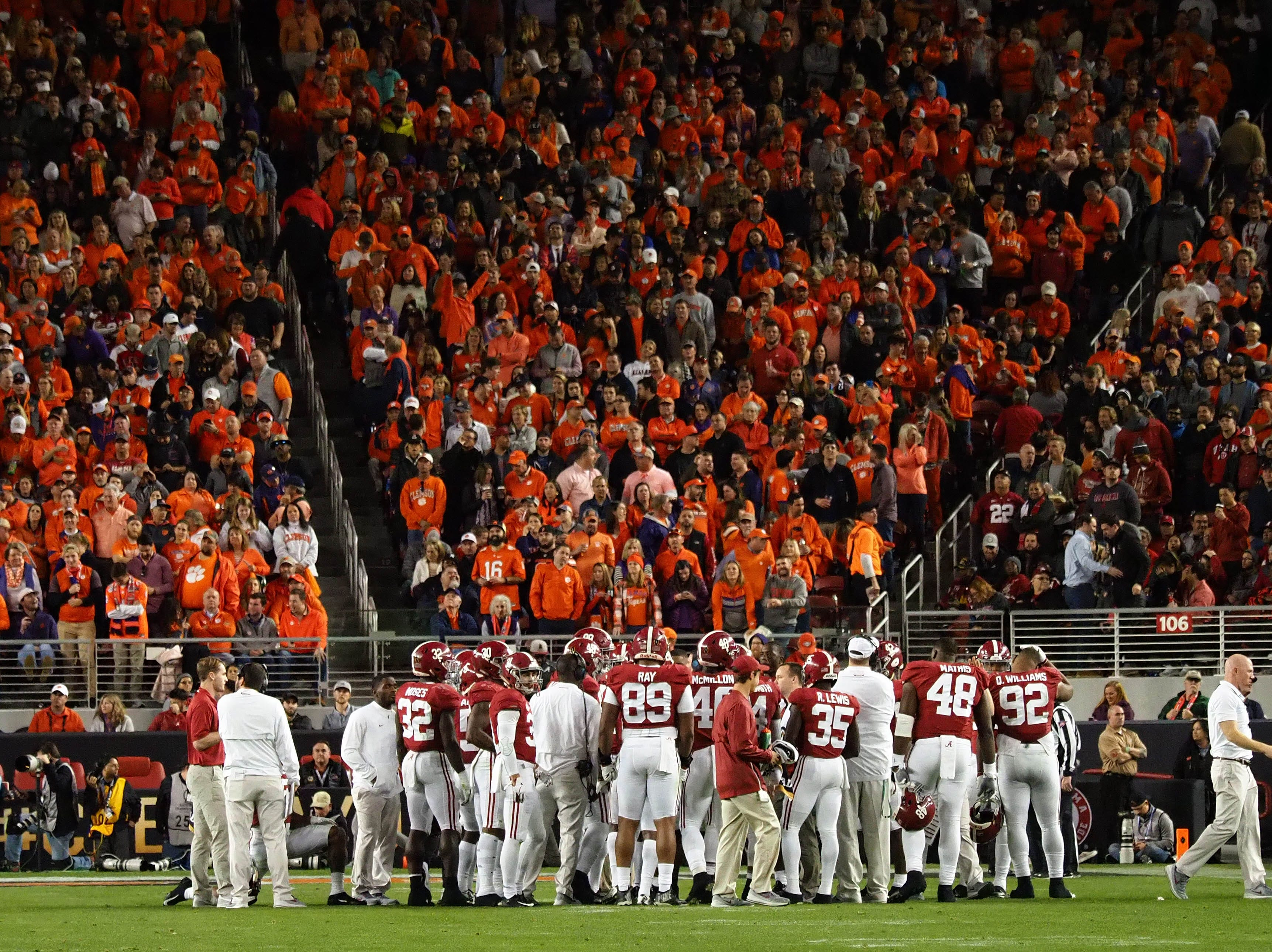 Clemson fans look on during an Alabama huddle.