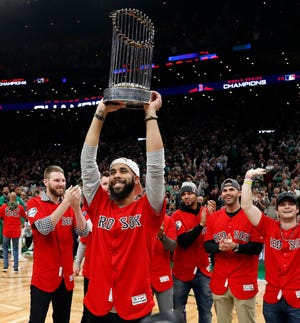 Red Sox pitcher David Price hoists the World Series trophy at TD Garden.