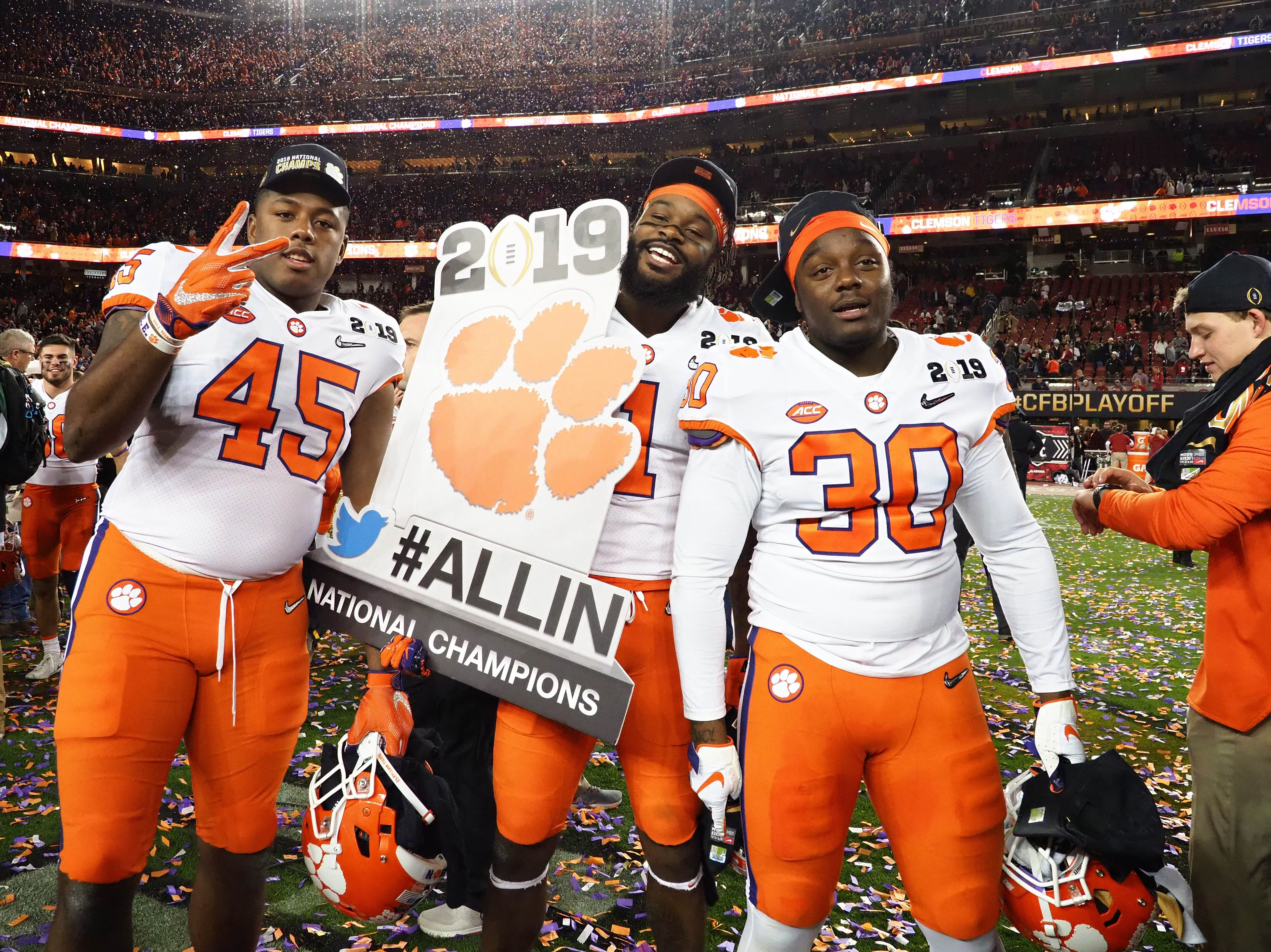 Clemson Tigers defensive end Chris Register (45) joins wide receiver Trevion Thompson (1) and linebacker Jalen Williams (30) in celebrating after winning the title.