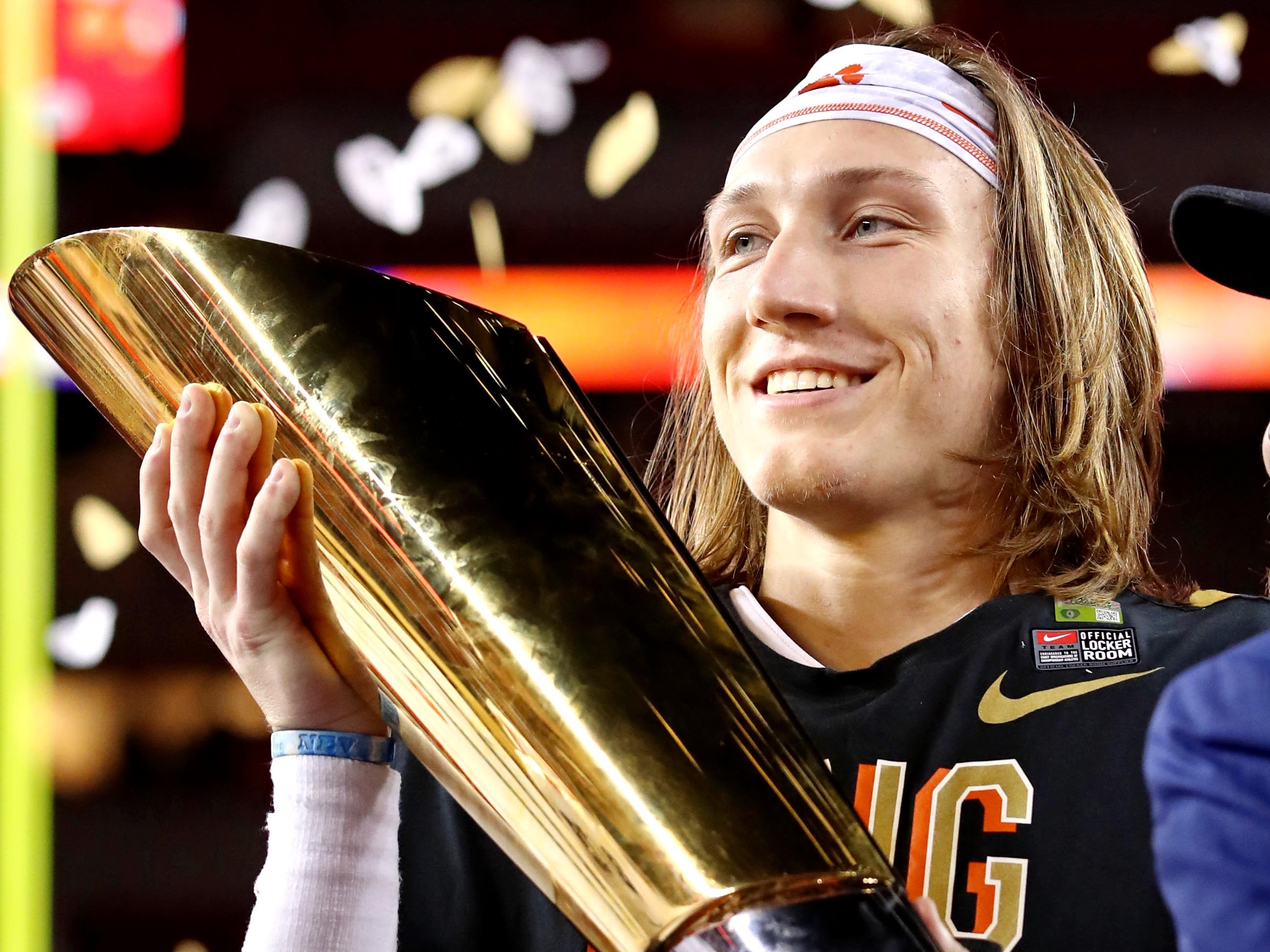 Clemson Tigers quarterback Trevor Lawrence celebrates with the national championship trophy after beating the Alabama Crimson Tide.