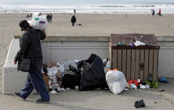 A woman walks past trash piled next to a garbage bin at Ocean Beach in San Francisco, Jan. 3, 2019.